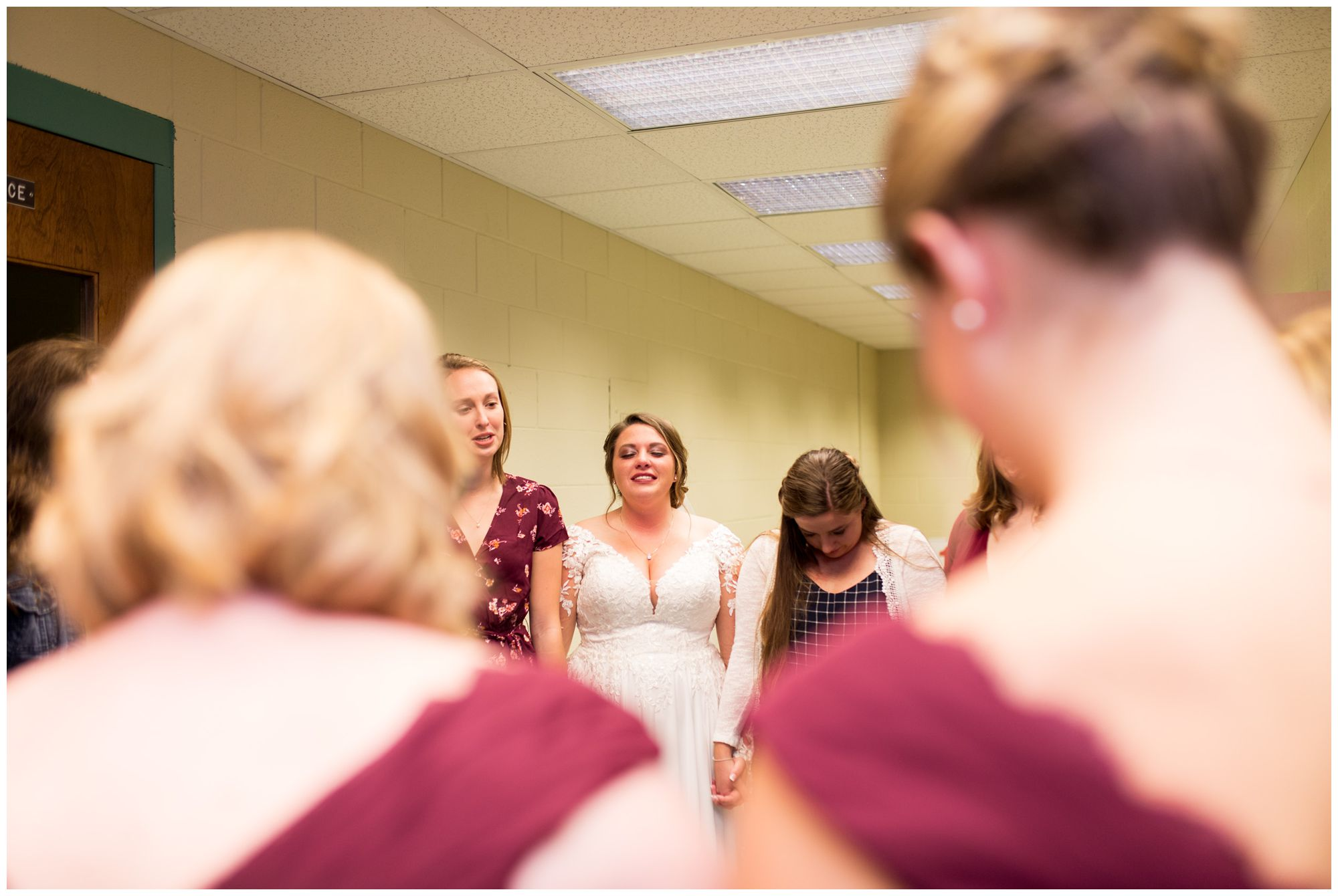 bride praying with friends before wedding ceremony at Zion Lutheran Church in Decatur