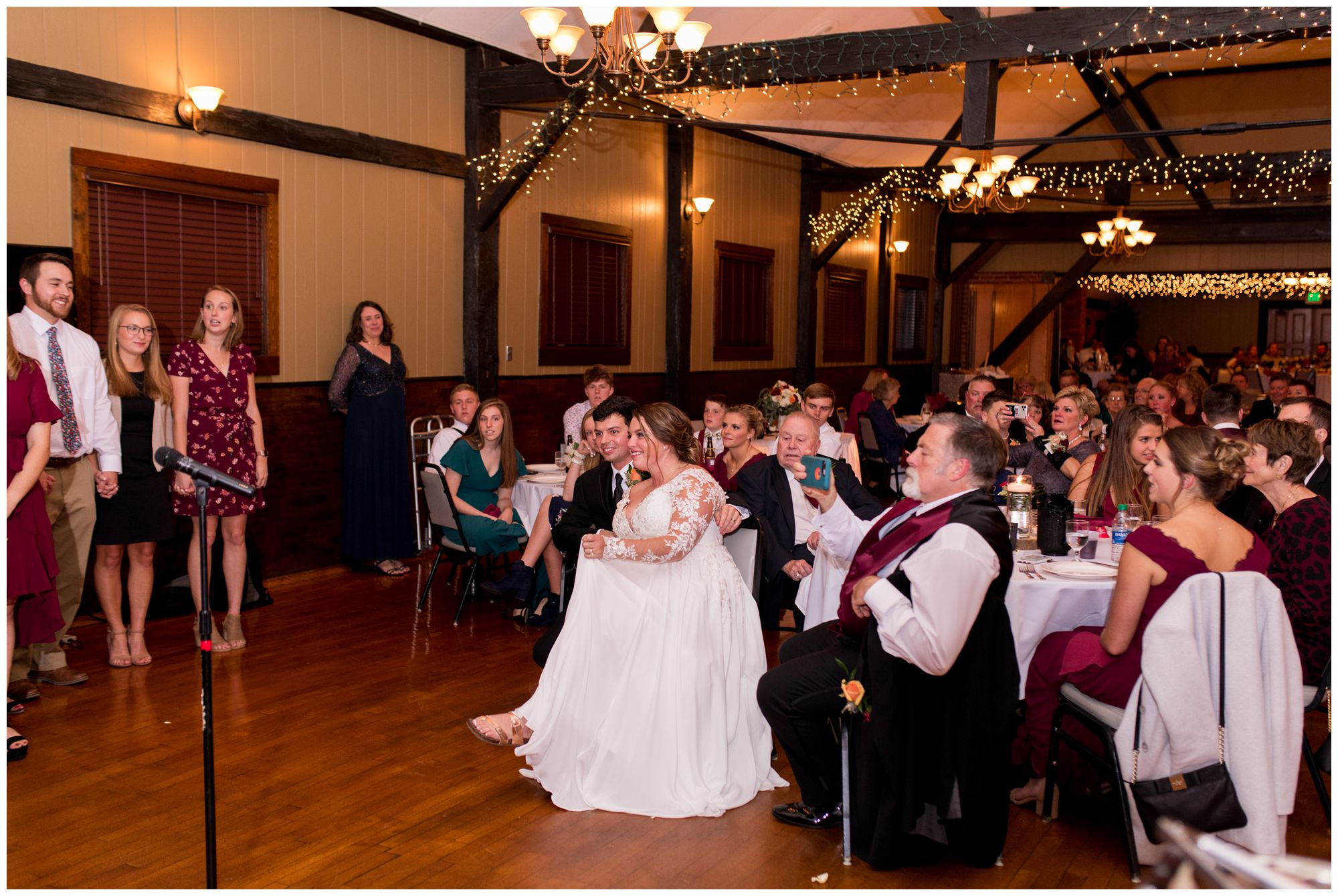 bride and groom listen to camp friends sing during wedding reception at Goeglein Homestead