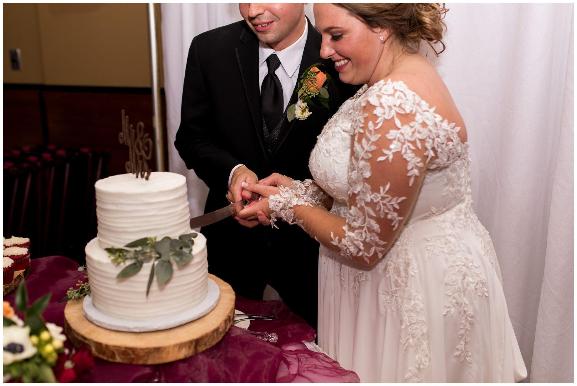 bride and groom cut wedding cake at Goeglein Homestead wedding reception in Fort Wayne