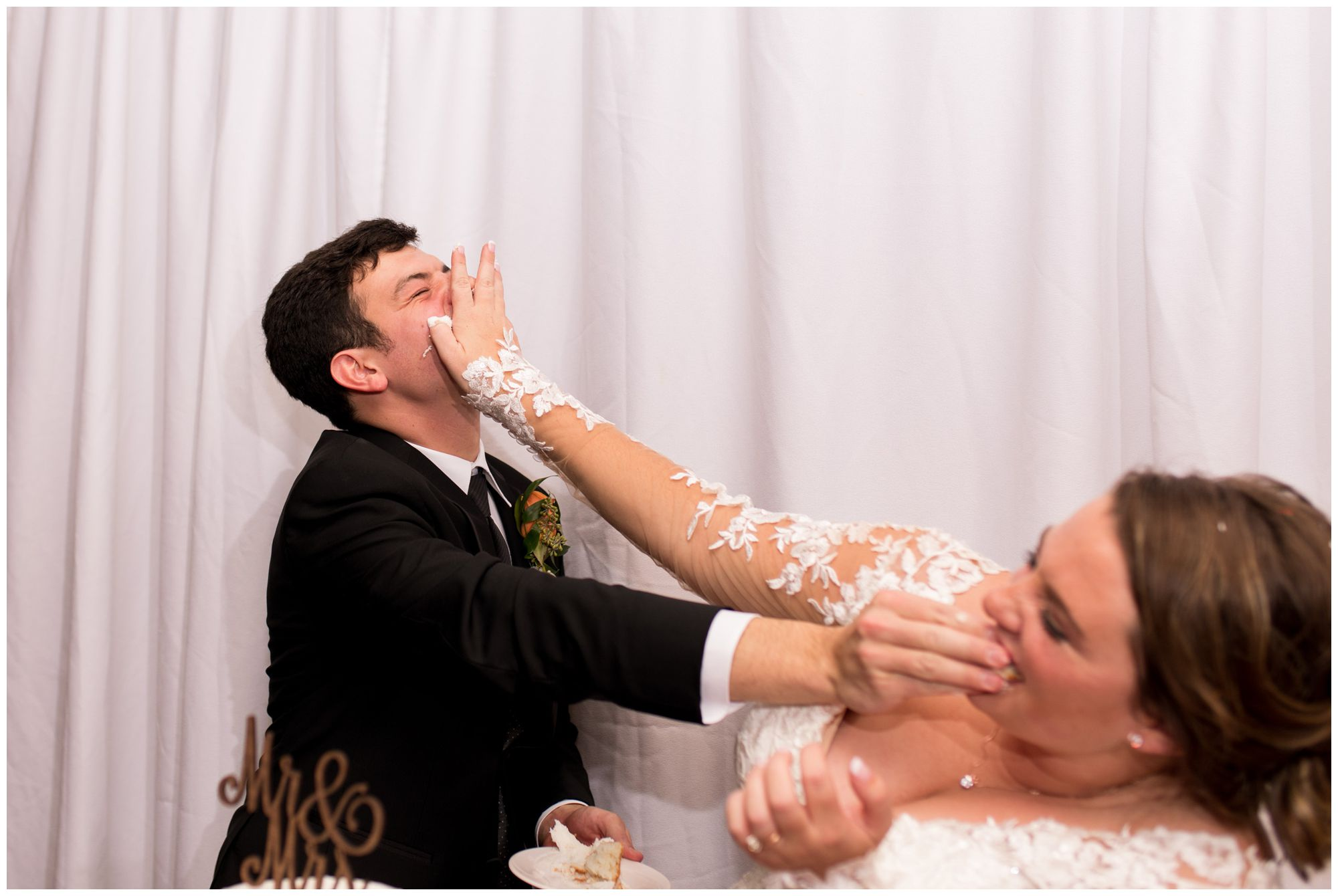 bride and groom cut cake and smash into each other's faces during Fort Wayne wedding reception
