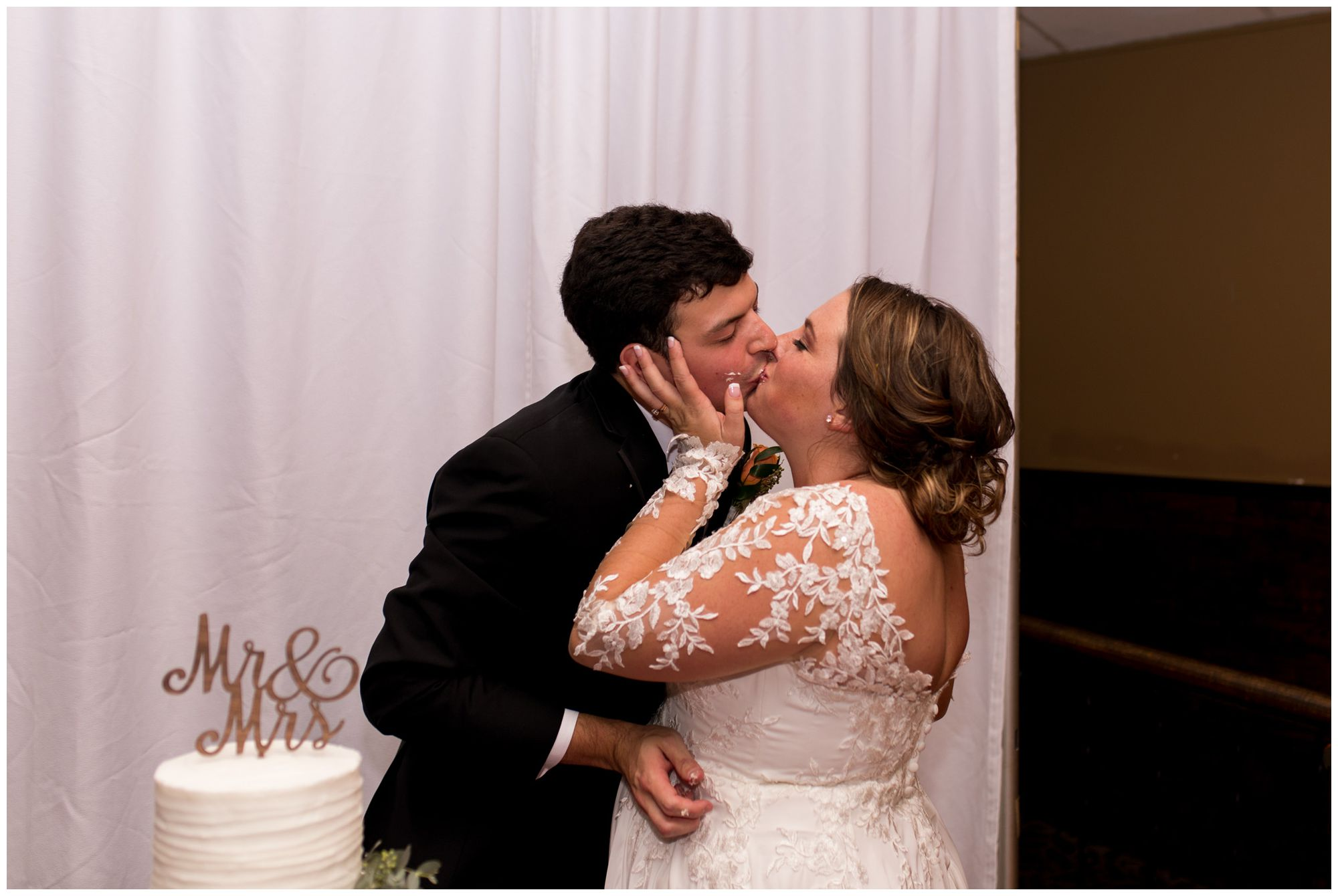 bride and groom kiss after cutting cake during Fort Wayne wedding reception