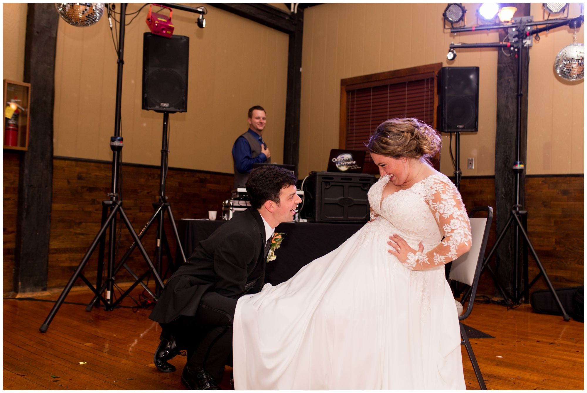 groom takes garter off bride's leg for garter toss at Goeglein Homestead