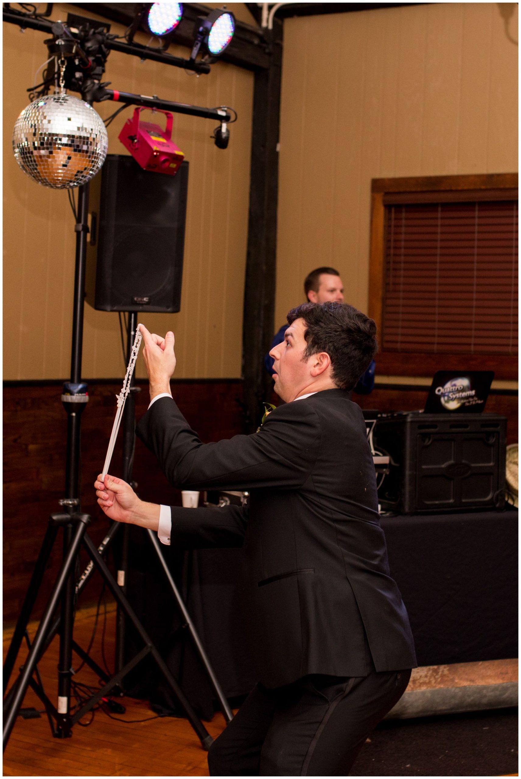 groom tosses garter during Fort Wayne wedding reception at Goeglein