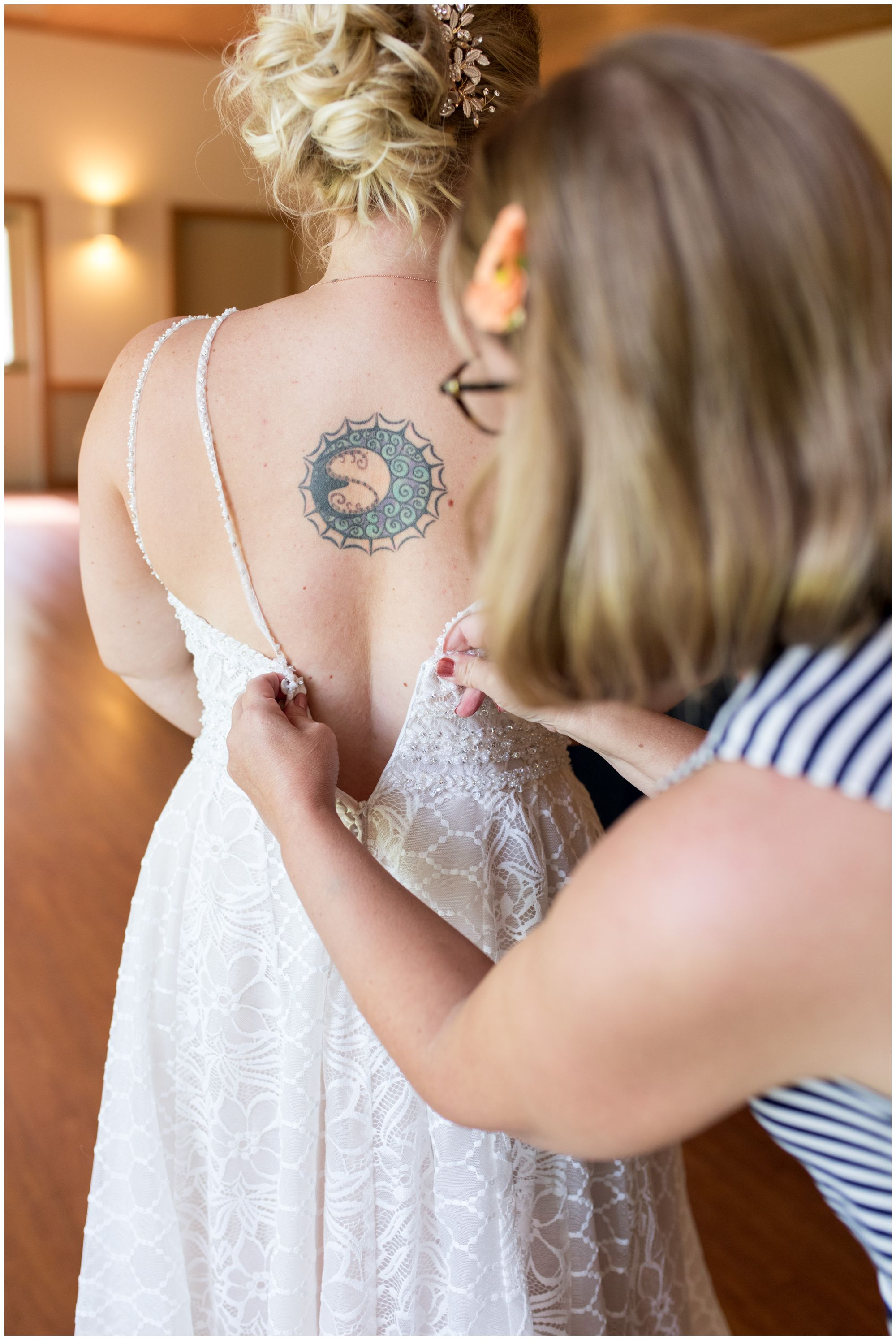 bride's mom zipping bride's dress before Noblesville wedding ceremony