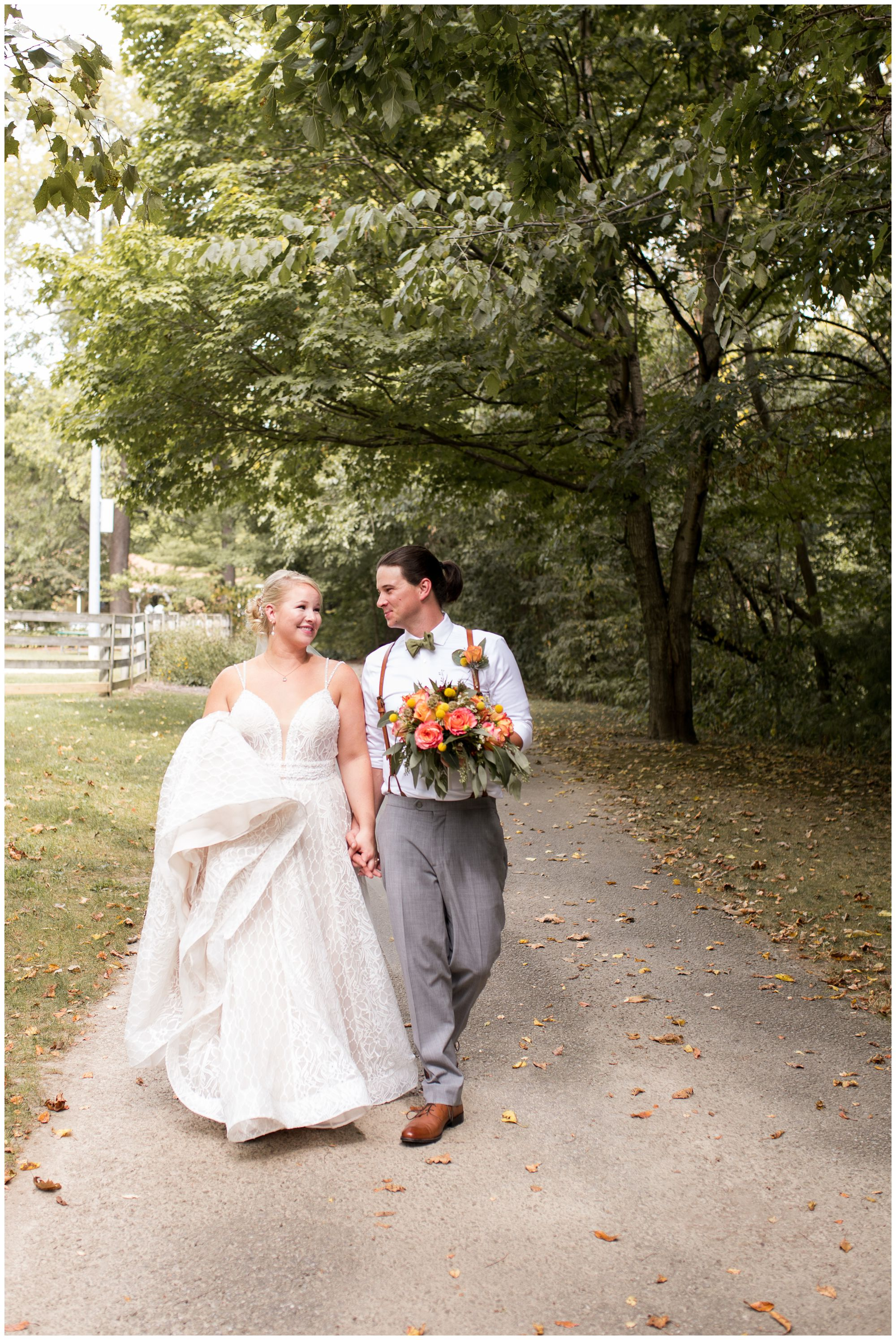 bride and groom walk hand in hand at Forest Park Inn in Noblesville