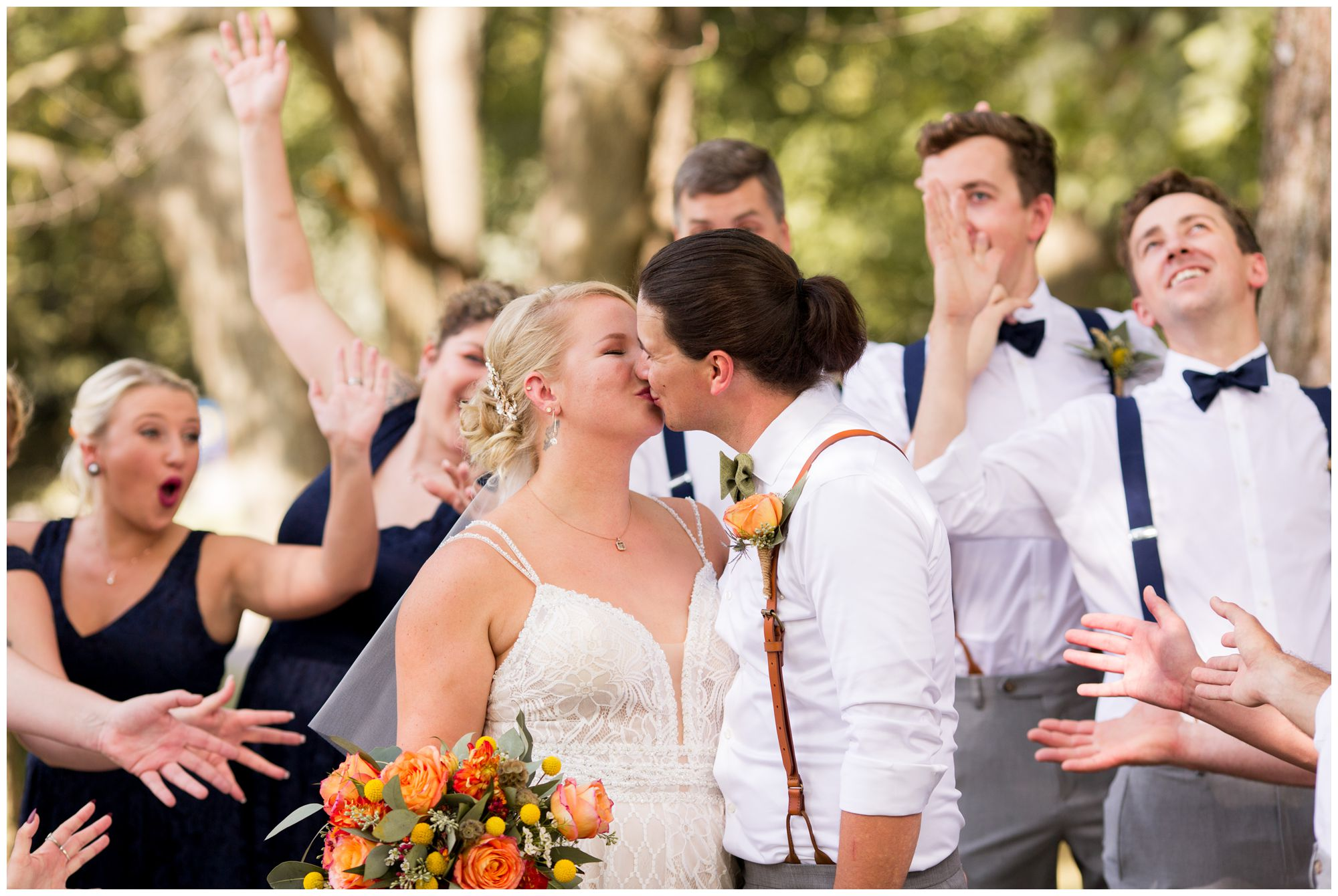 bride and groom kiss while wedding party cheers in Noblesville Indiana