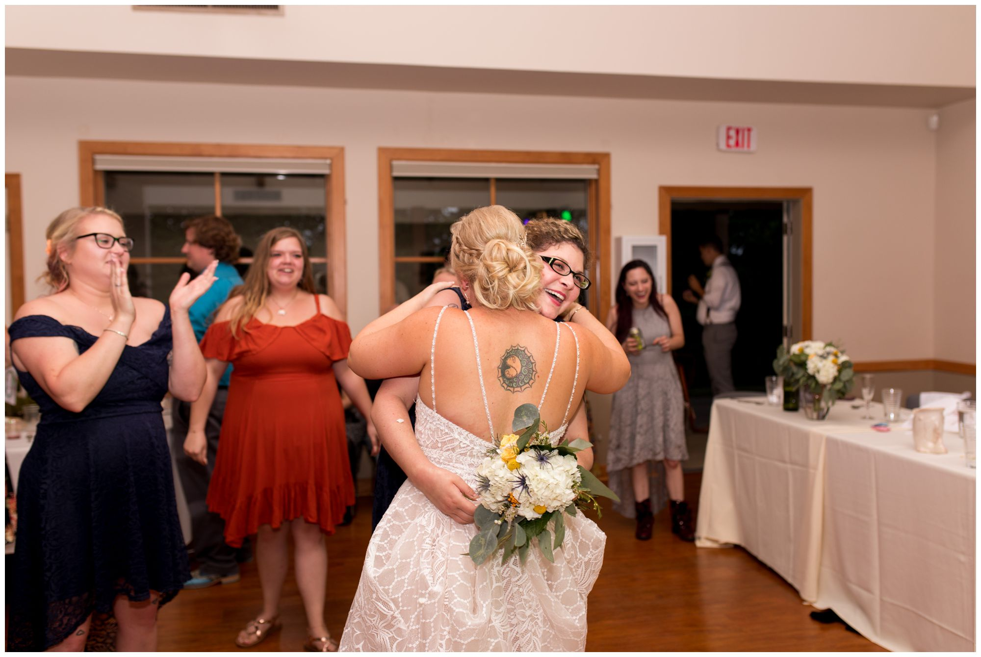 bride and maid of honor hug after bouquet toss