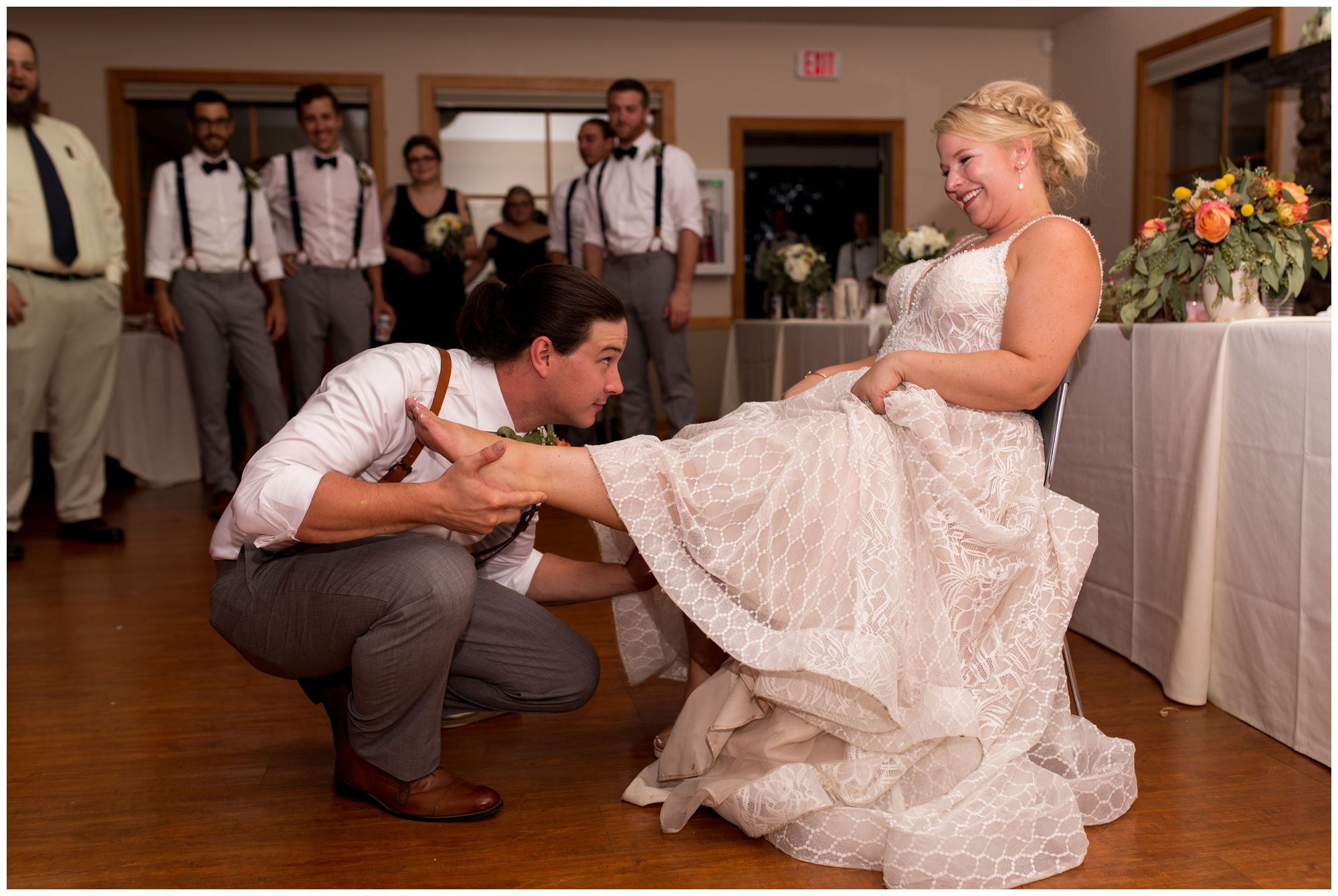 groom removes garter from bride's leg during Forest Park Inn wedding reception