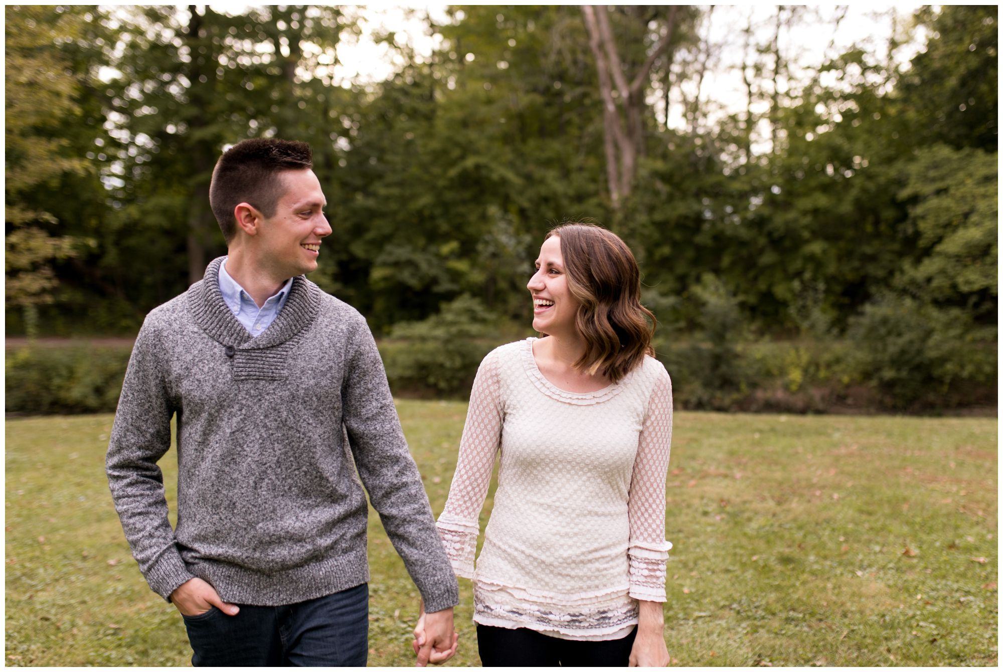 bride and groom walk hand in hand during Kokomo engagement session at Highland Park