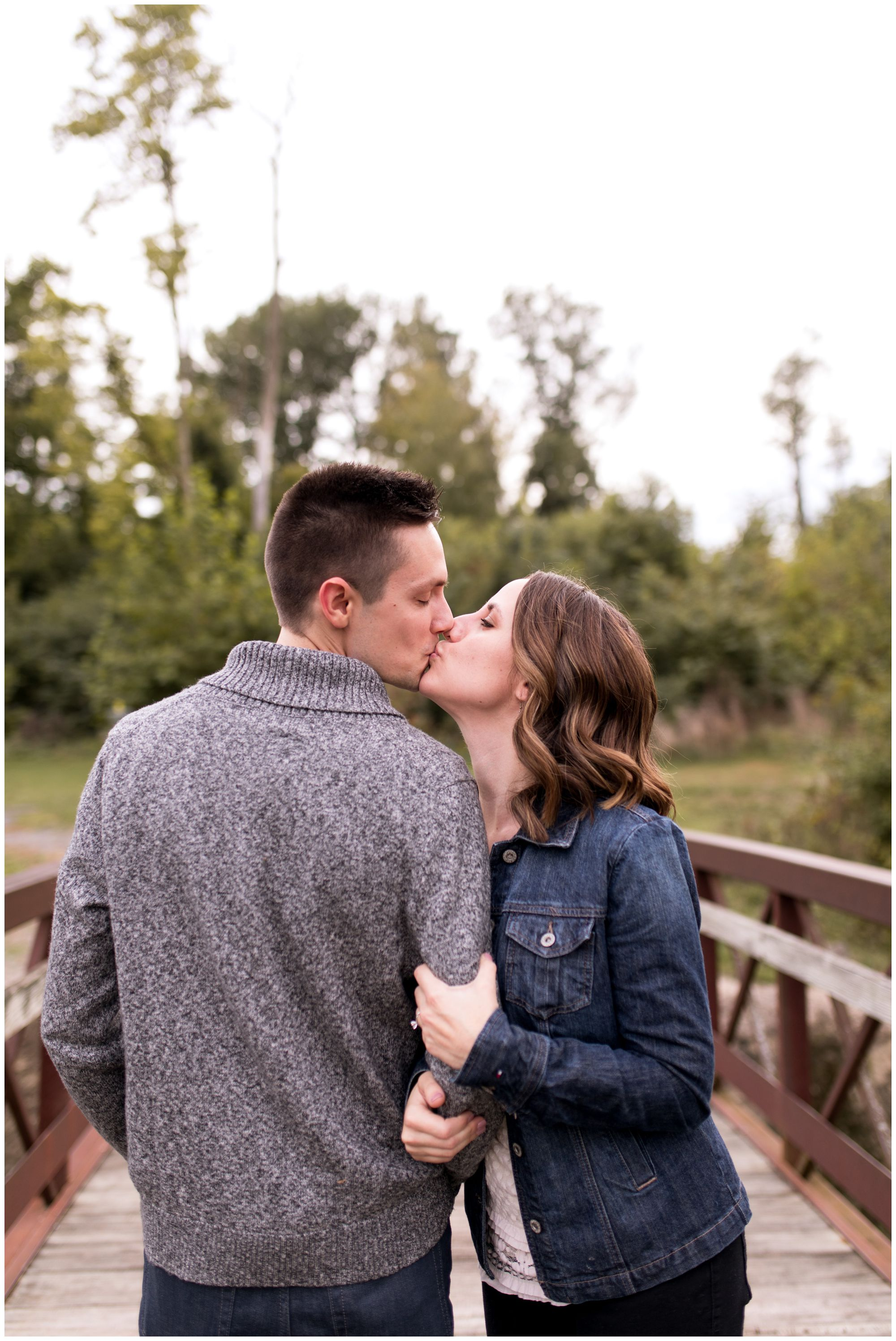 bride and groom kiss holding hands during Kokomo engagement session