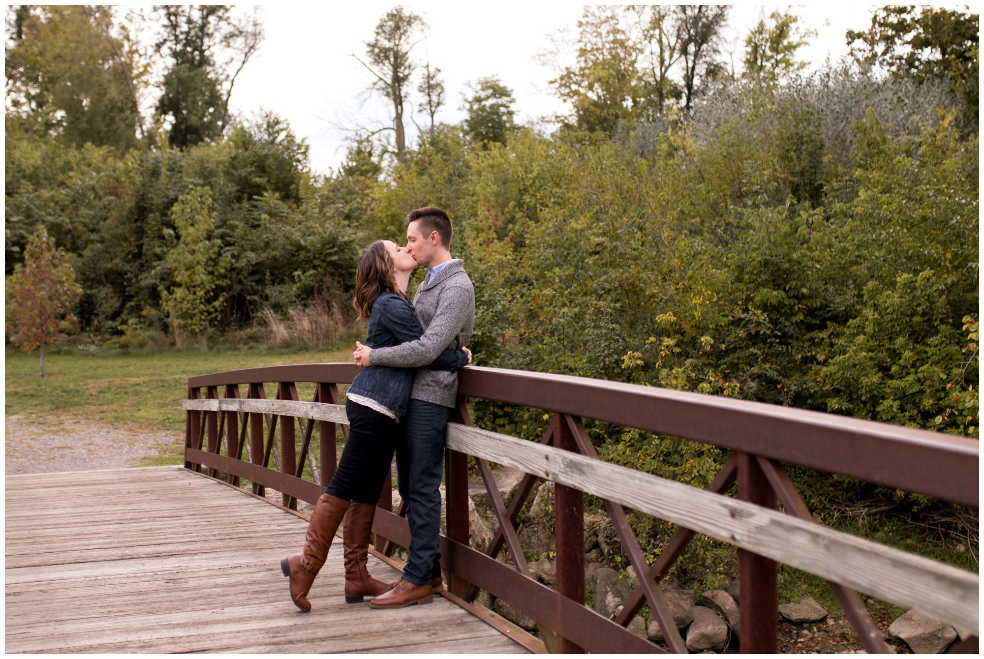 bride and groom kiss on bridge at Highland Park during Kokomo engagement session