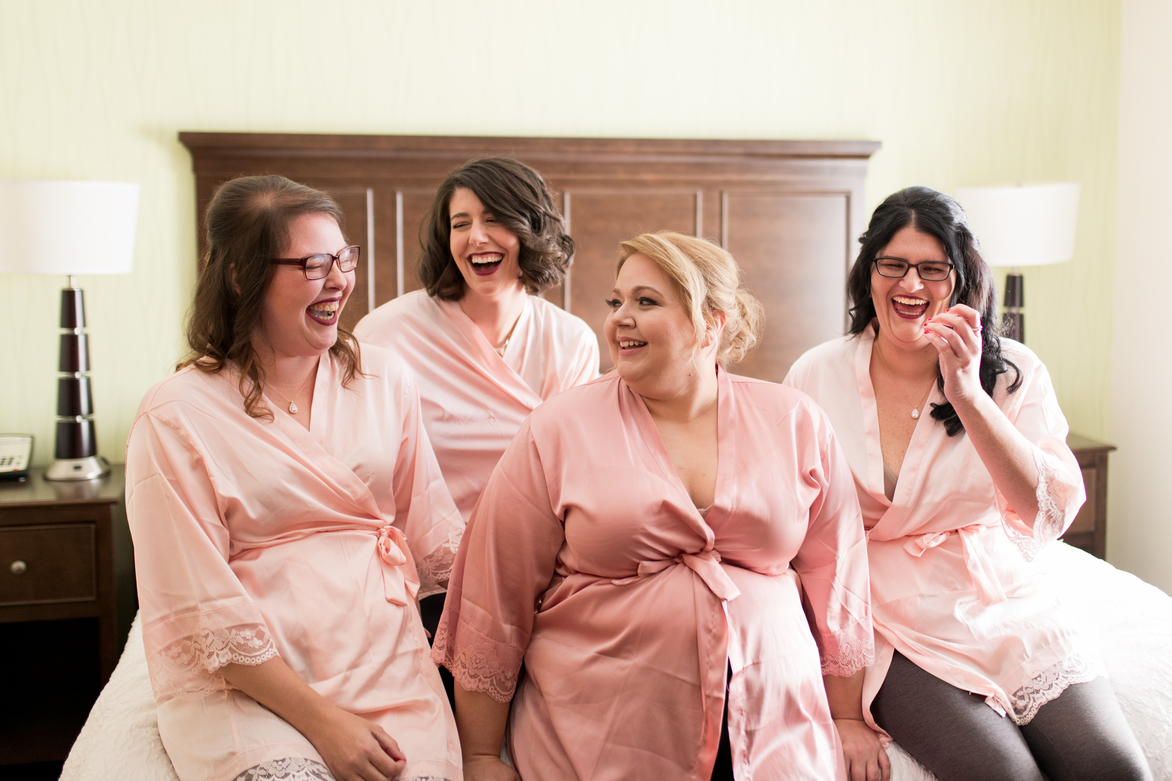 bride with bridesmaids laughing before getting dressed for wedding in Kokomo Indiana