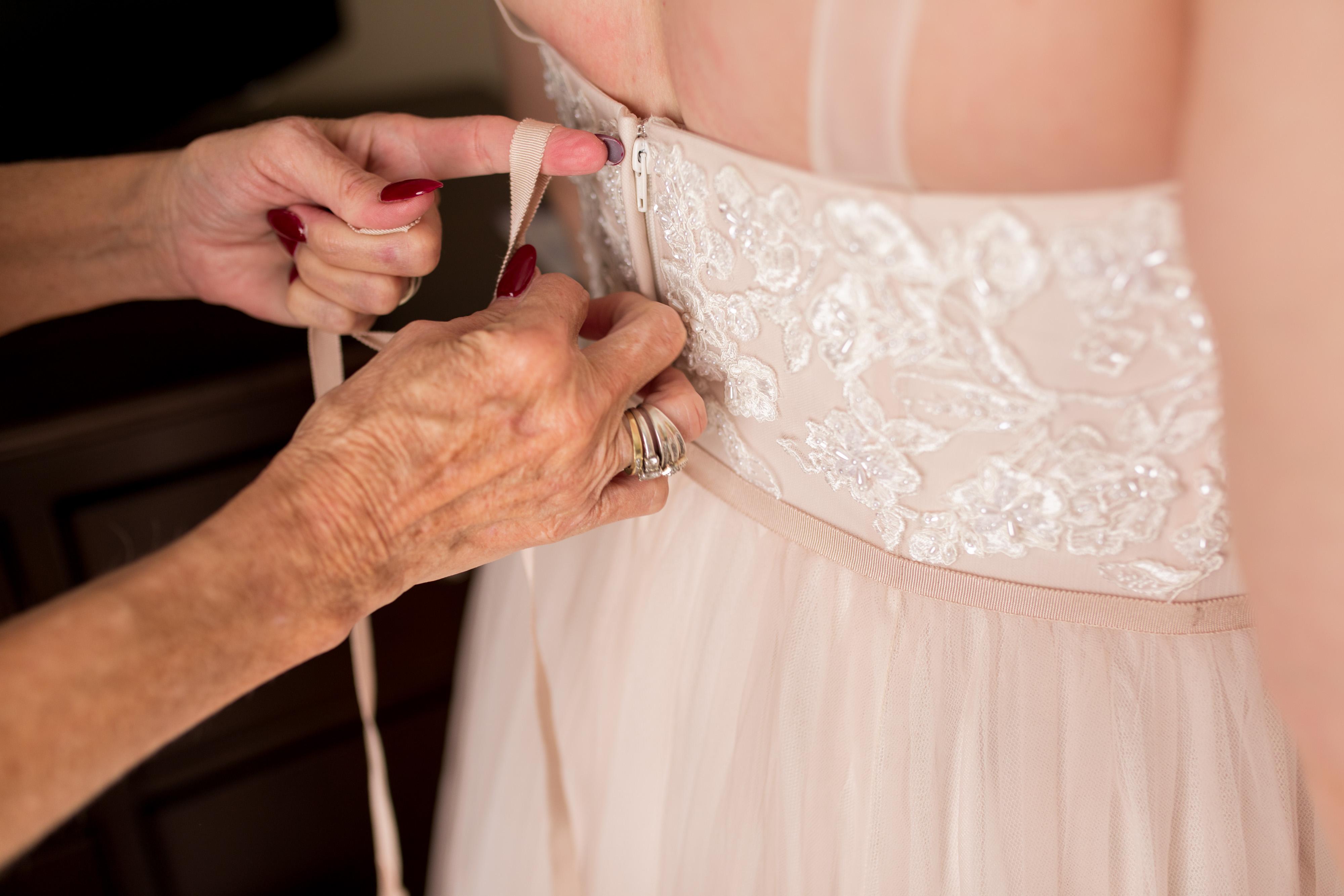 mother ties ribbon on bride's dress before Kokomo Indiana wedding