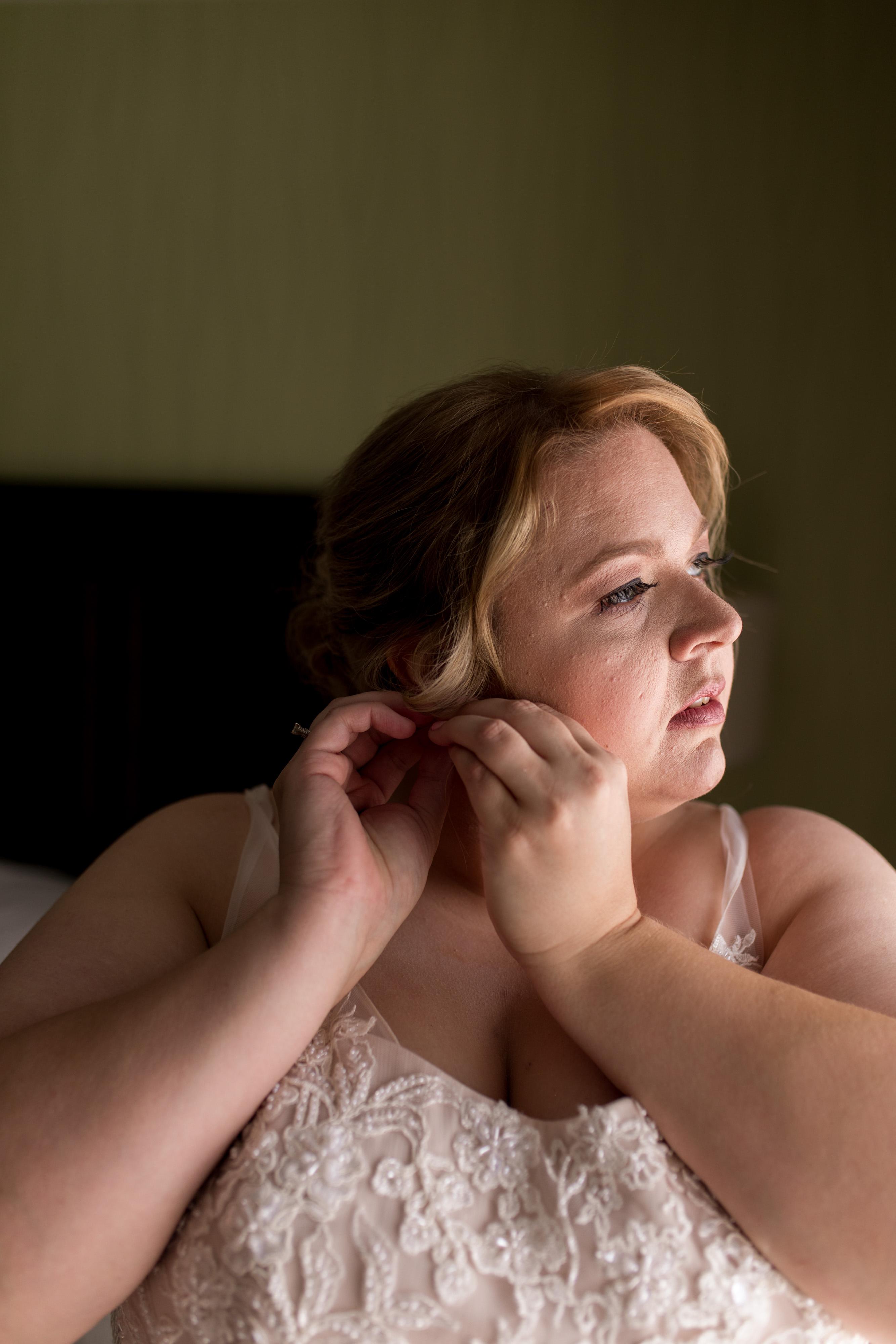 bride puts on earrings before Kokomo wedding