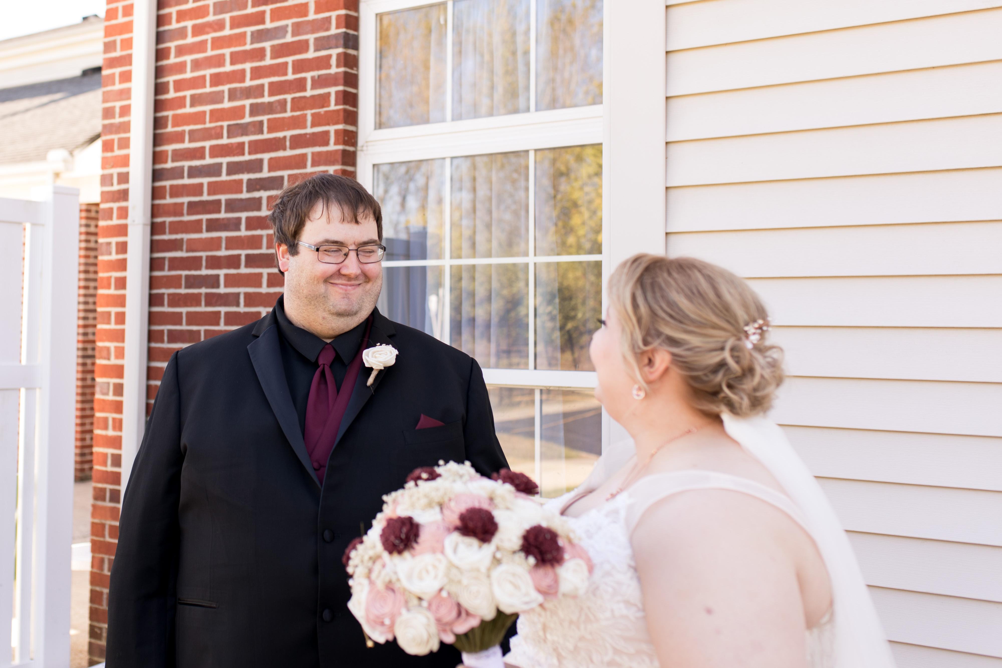 groom smiles at bride during first look before Kokomo wedding