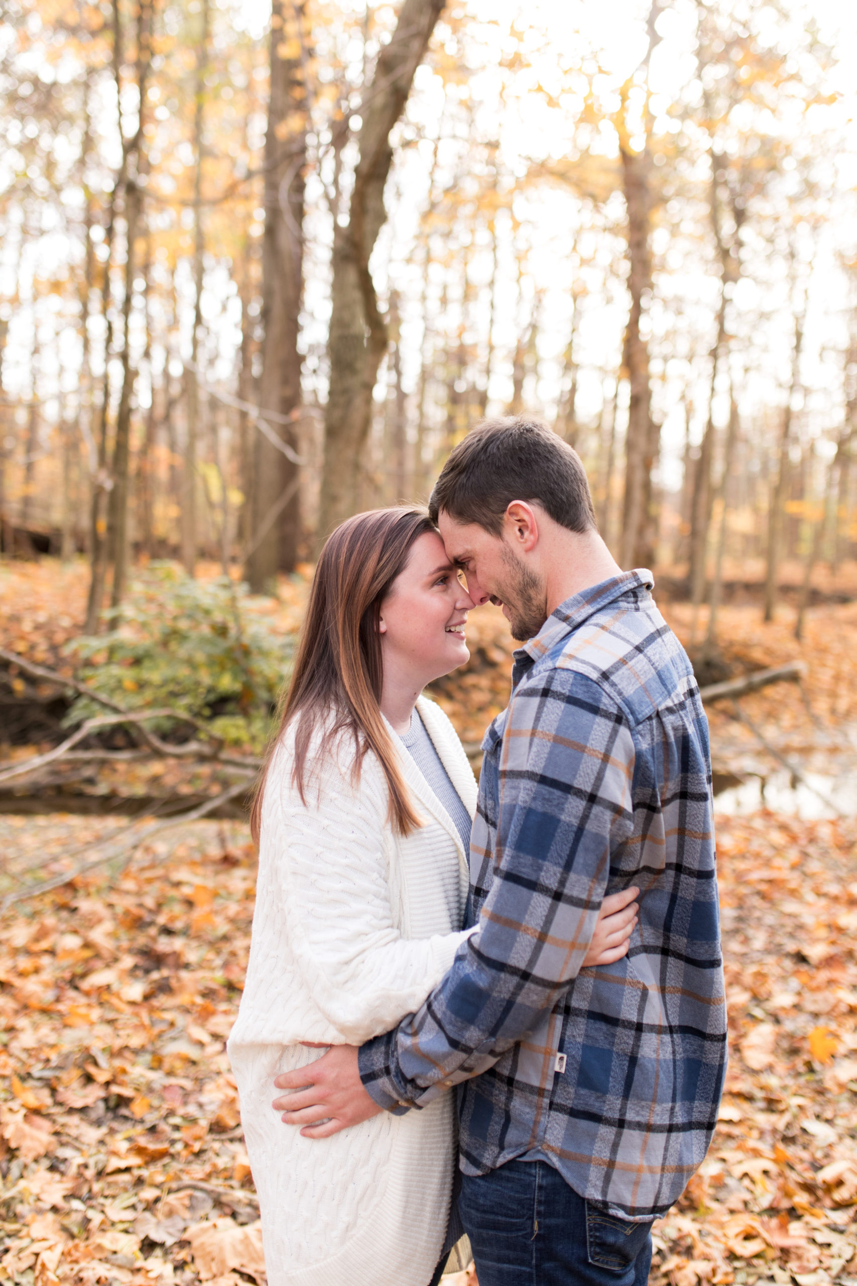 bride and groom stand nose to nose during Kokomo engagement session at Jackson Morrow Park