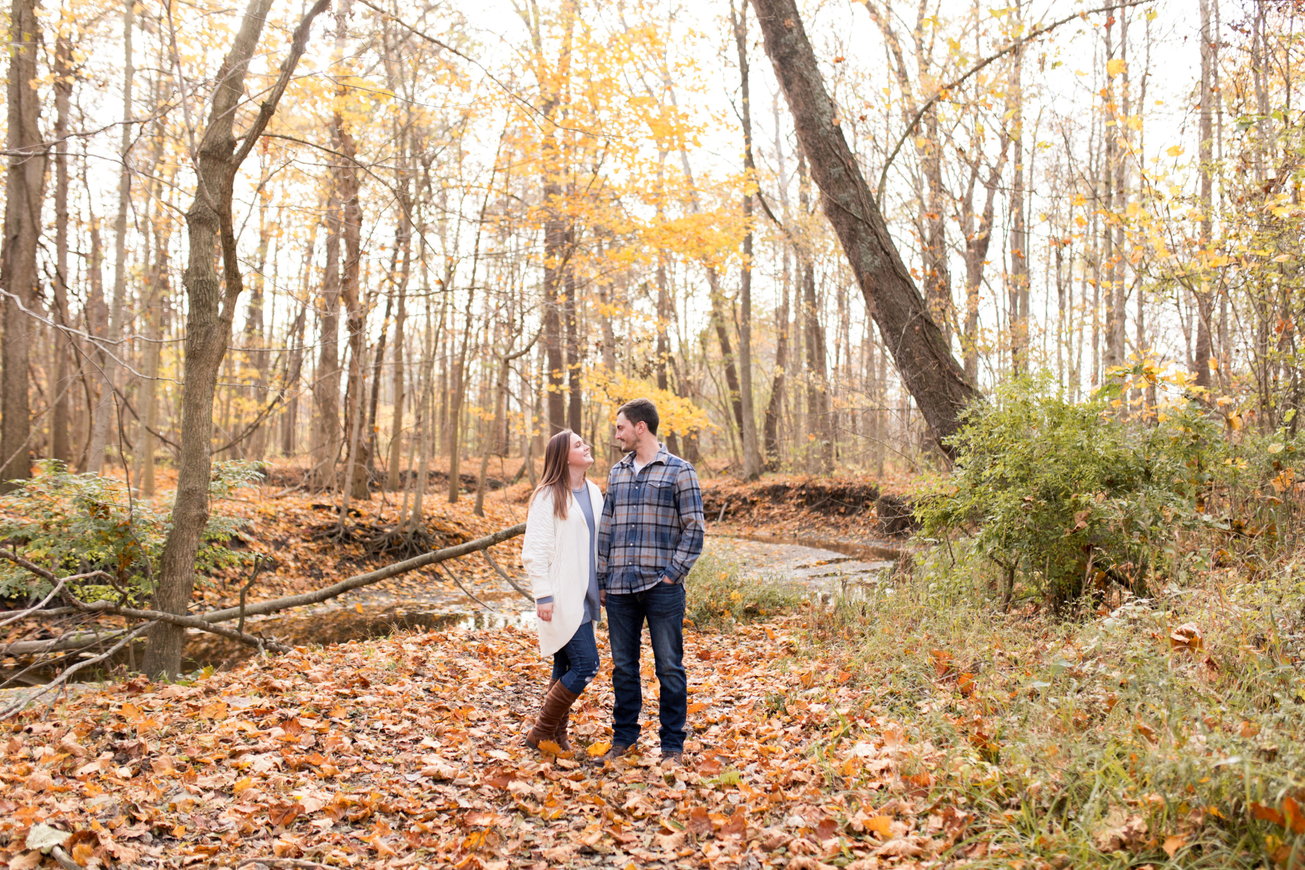 bride and groom stand with fall leaves in background during Jackson Morrow engagement session in Kokomo