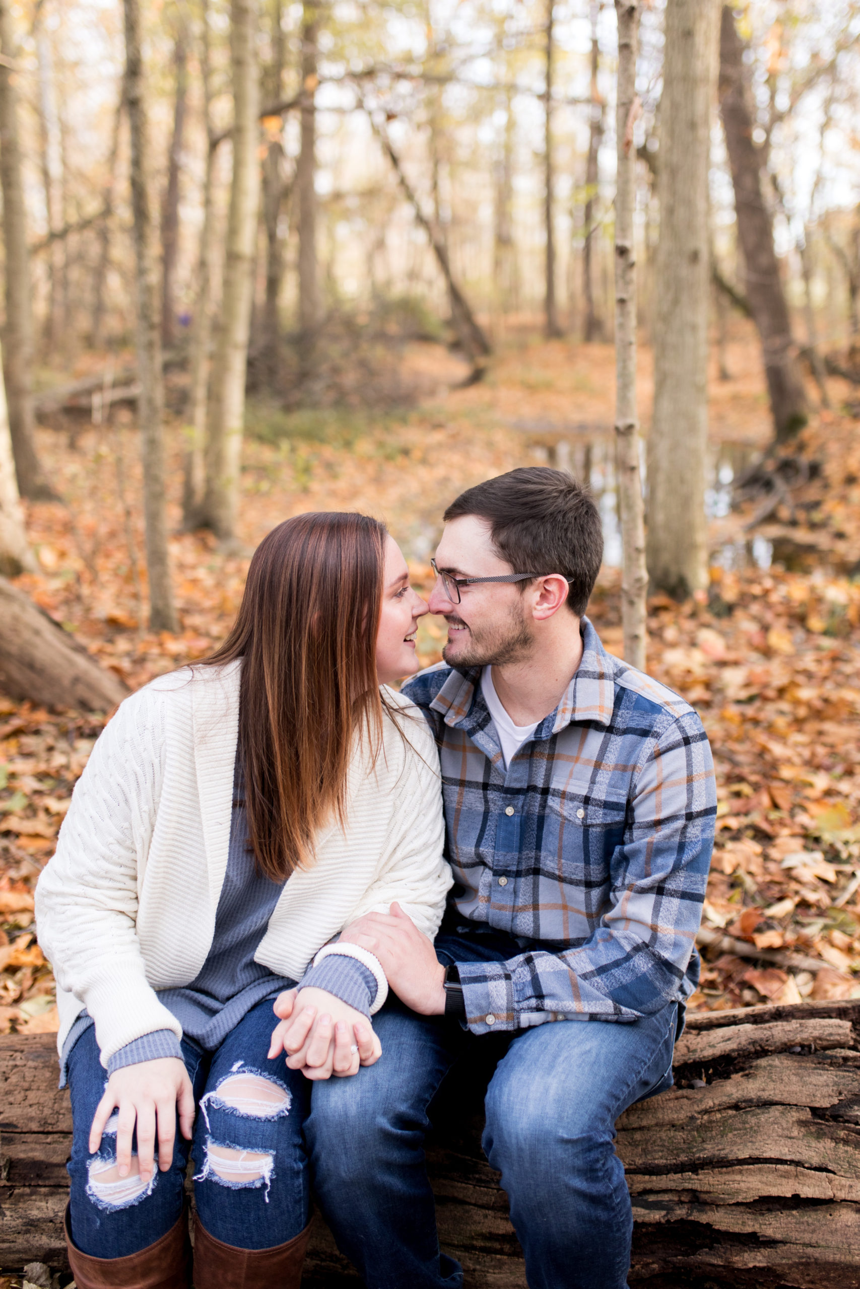 couple sits on tree log during fall engagement session at Jackson Morrow Park in Kokomo