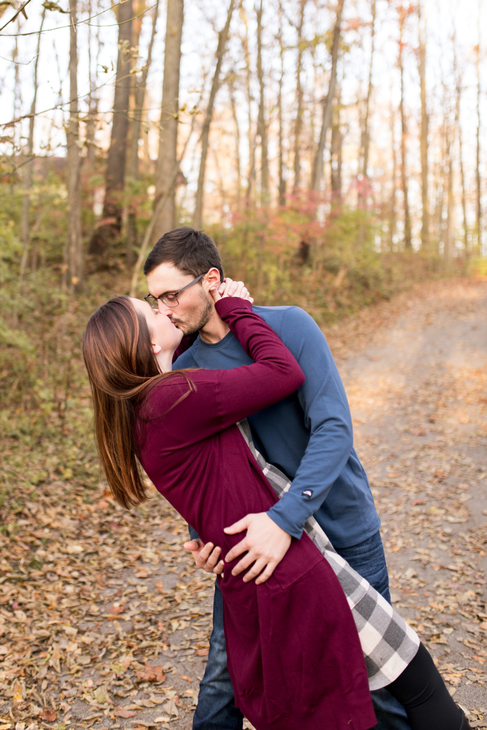 groom dips bride for kiss during engagement session at Jackson Morrow Park in Kokomo