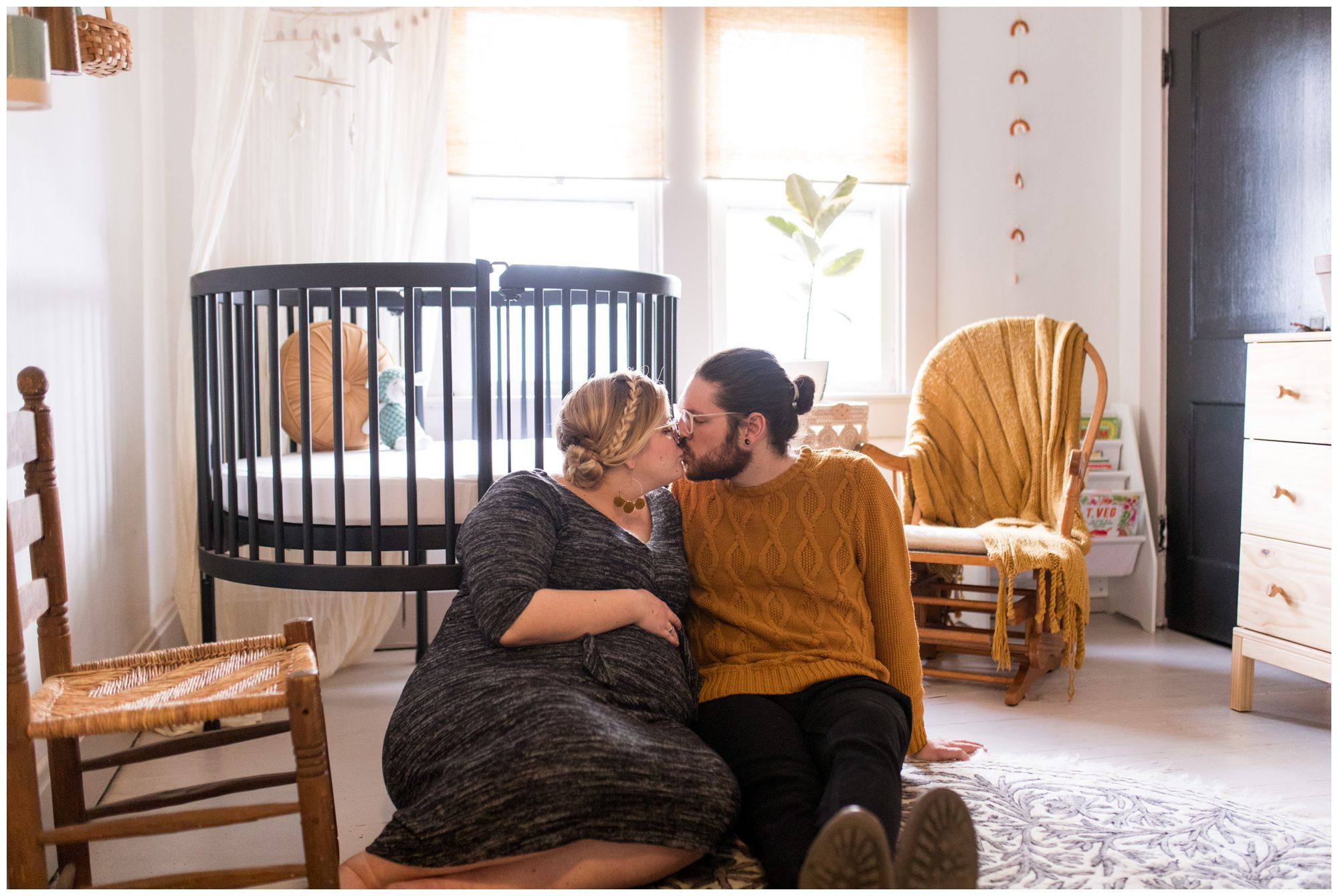 mom and dad kiss in nursery during Indianapolis maternity session