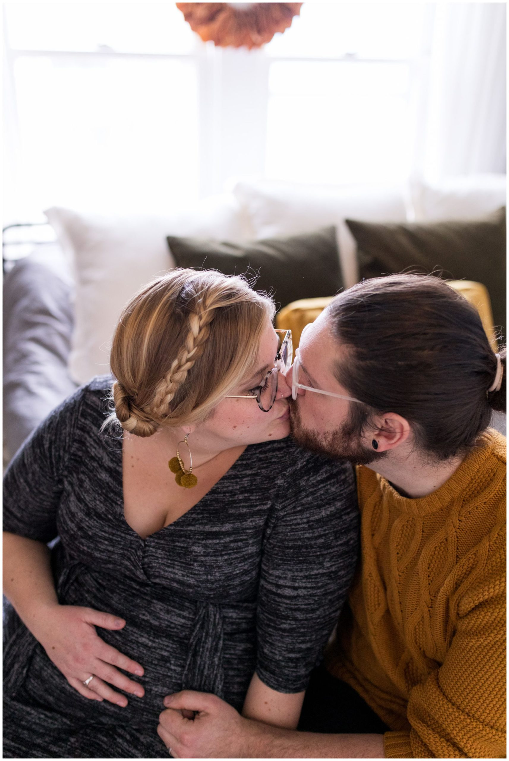 mom and dad kiss during home maternity session in Indianapolis