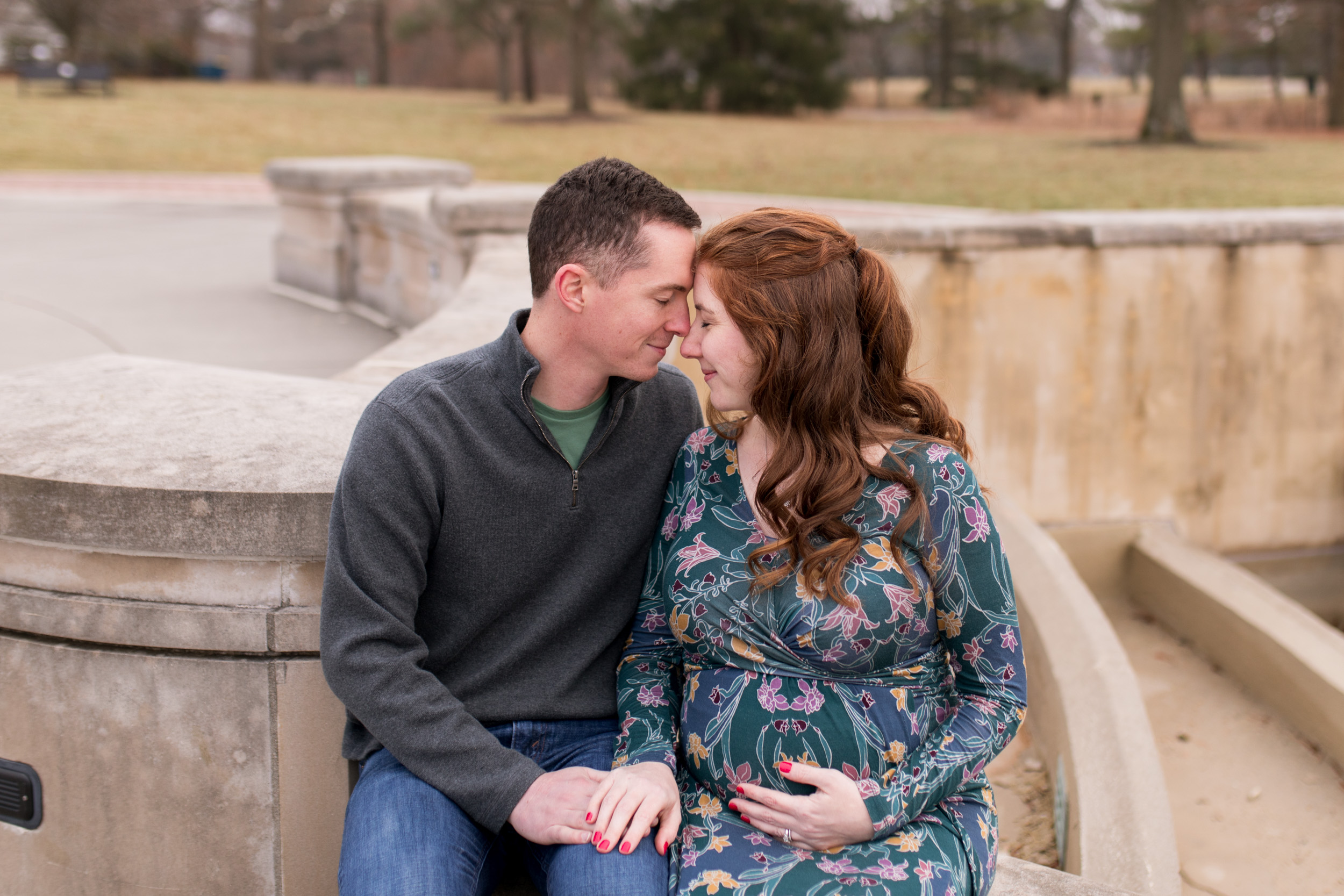 mom and dad with foreheads together during maternity photos at Coxhall Gardens in Carmel