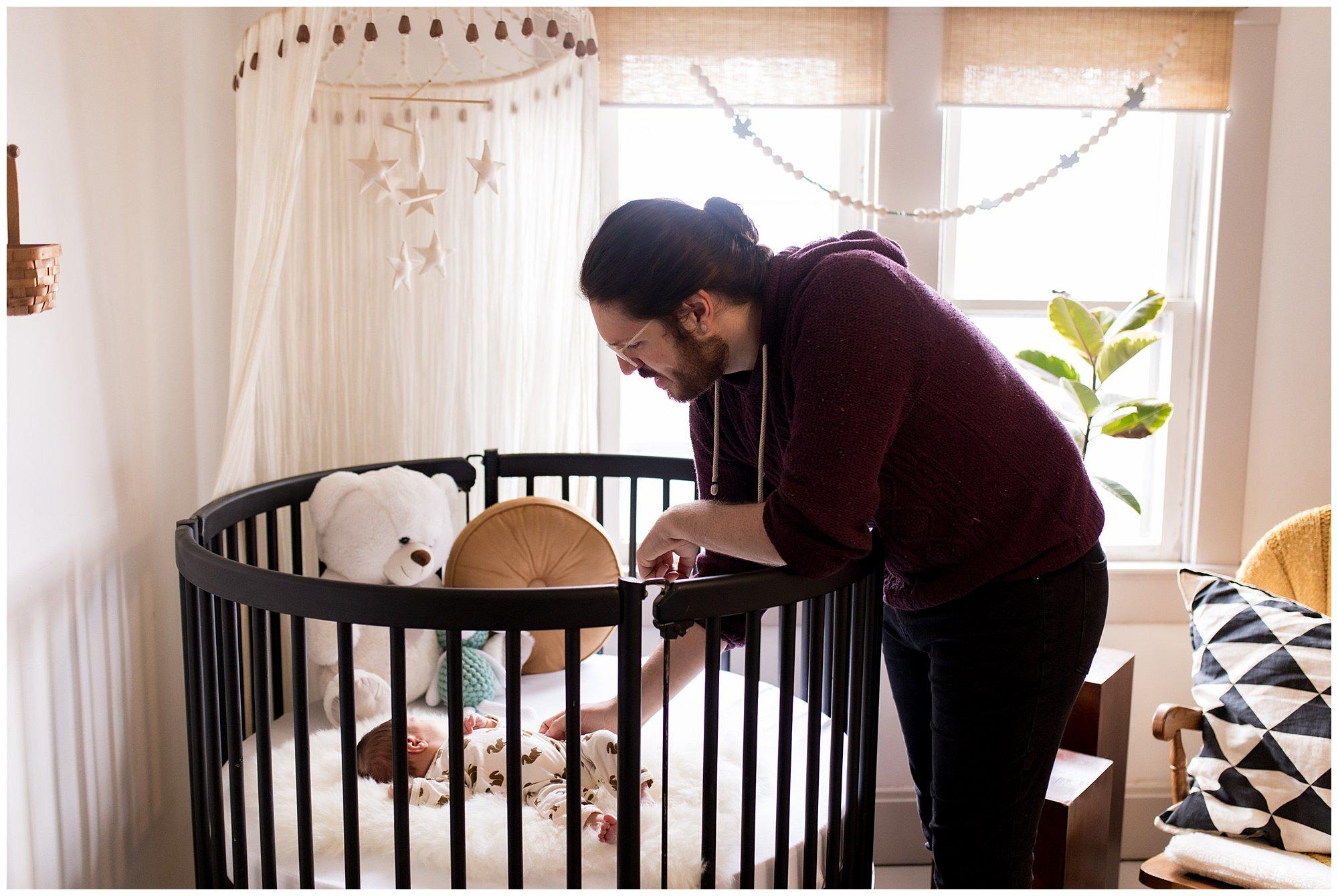 dad reaches into newborn's circular crib