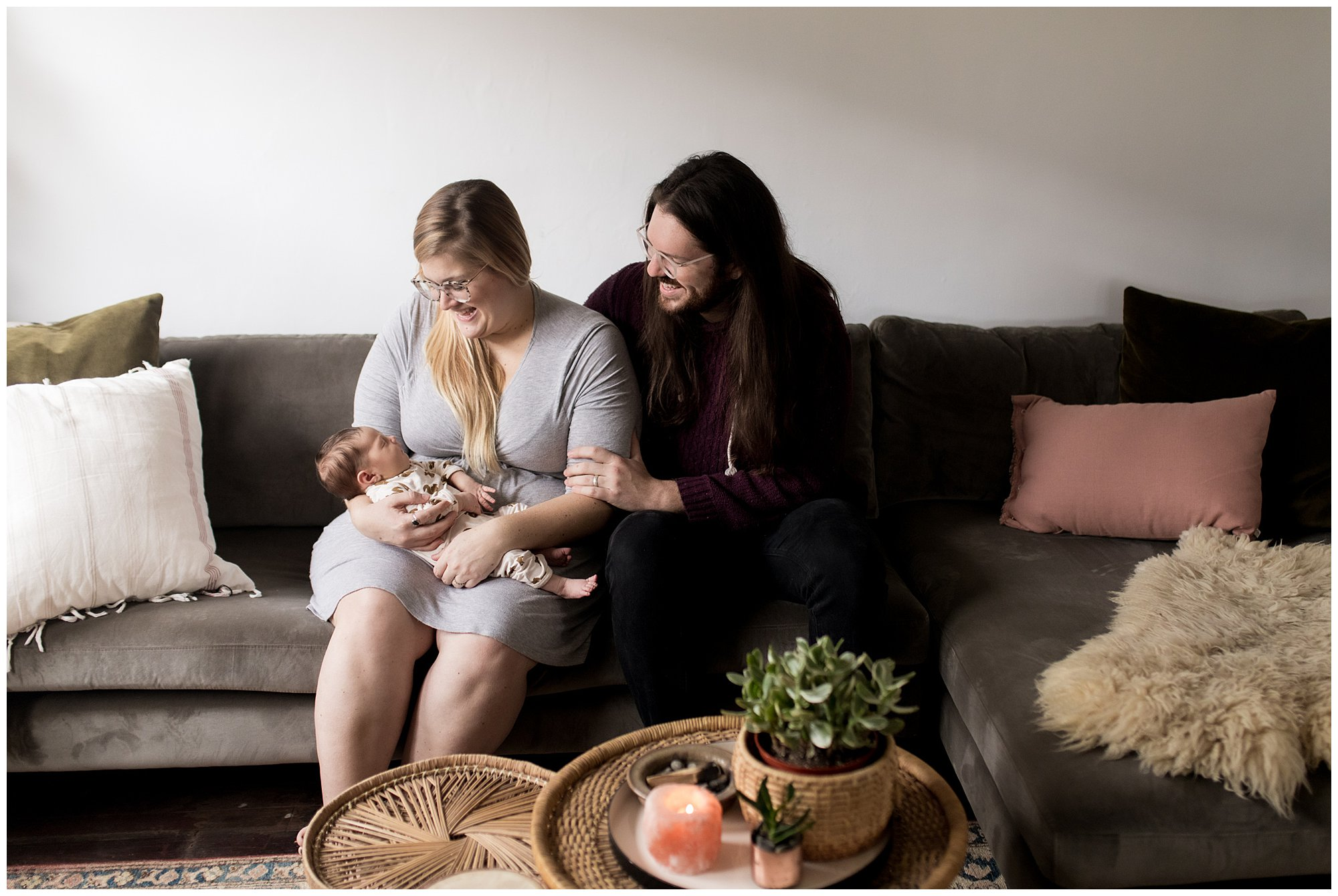 mom and dad hold baby on couch in living room