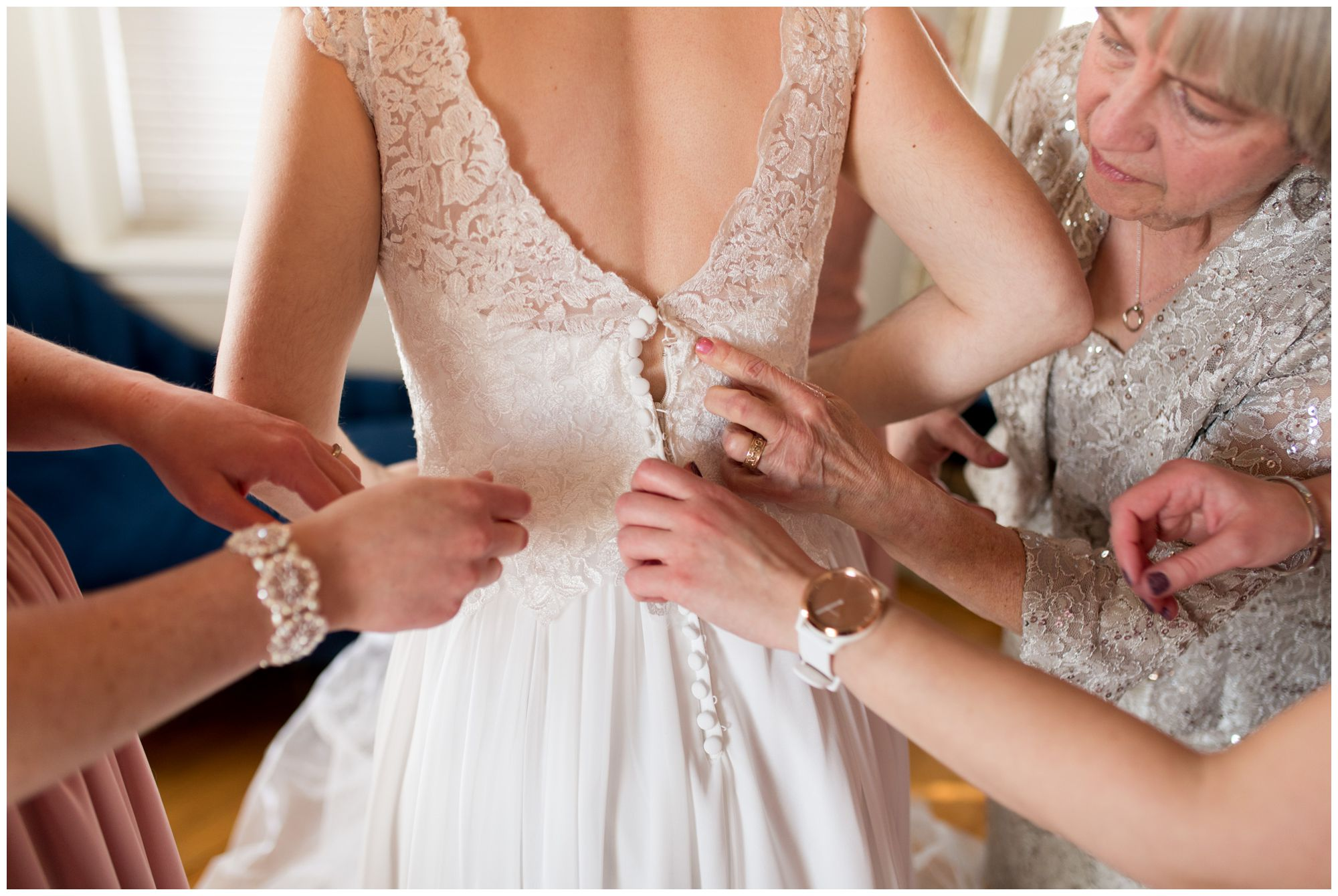bridesmaids buttoning bride's dress at Bread & Chocolate venue before wedding
