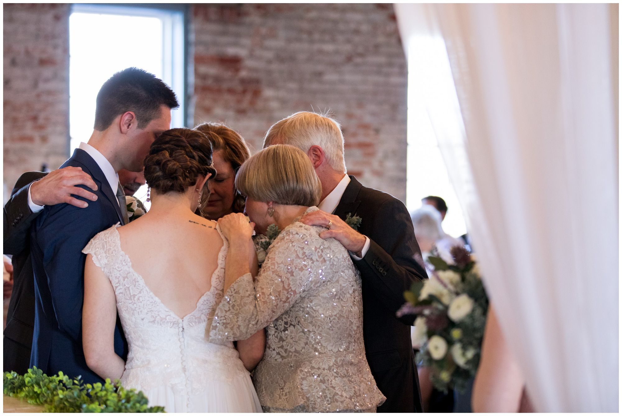bride and groom's parents pray over couple during Goshen wedding ceremony