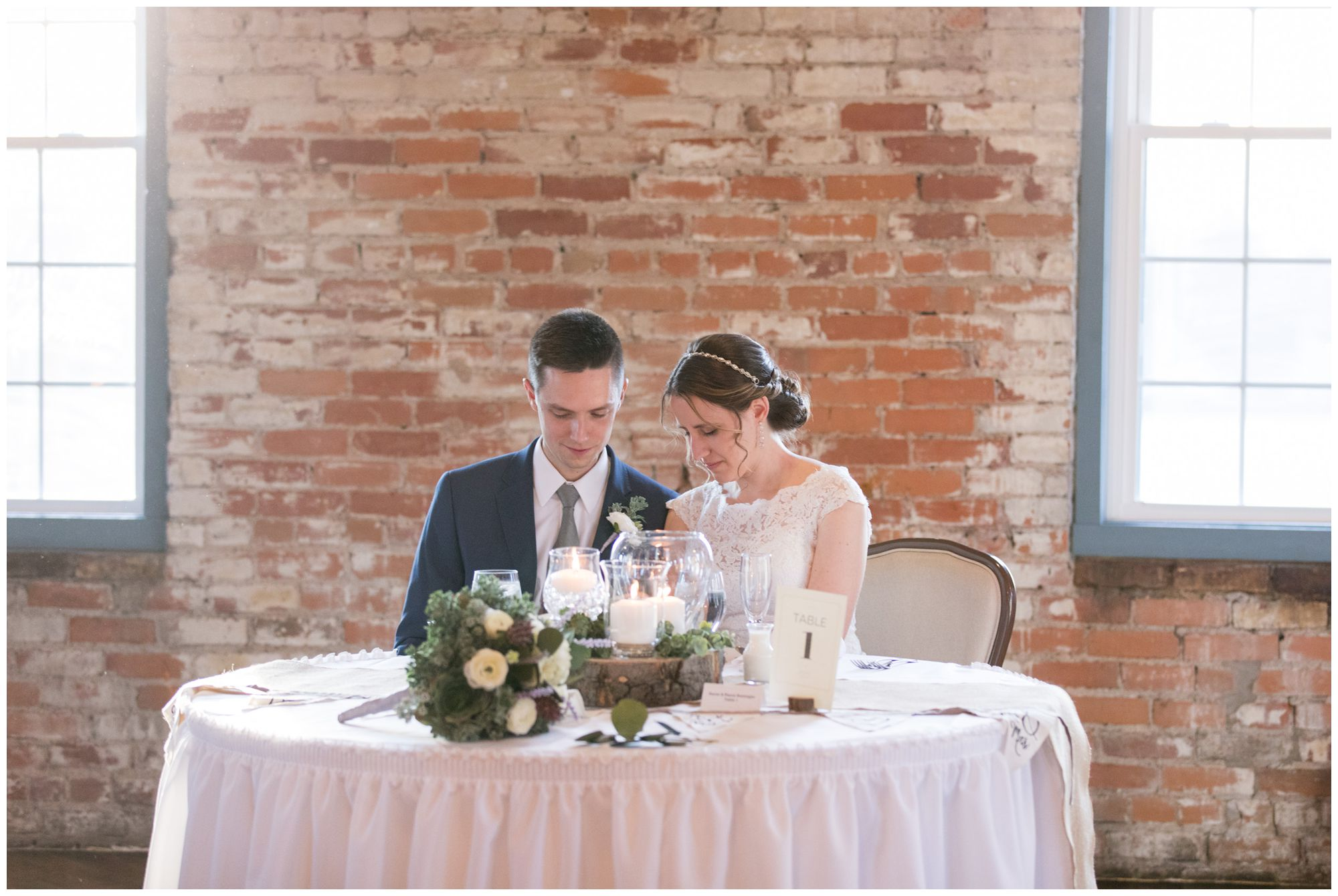 bride and groom pray together before dinner at Goshen wedding reception