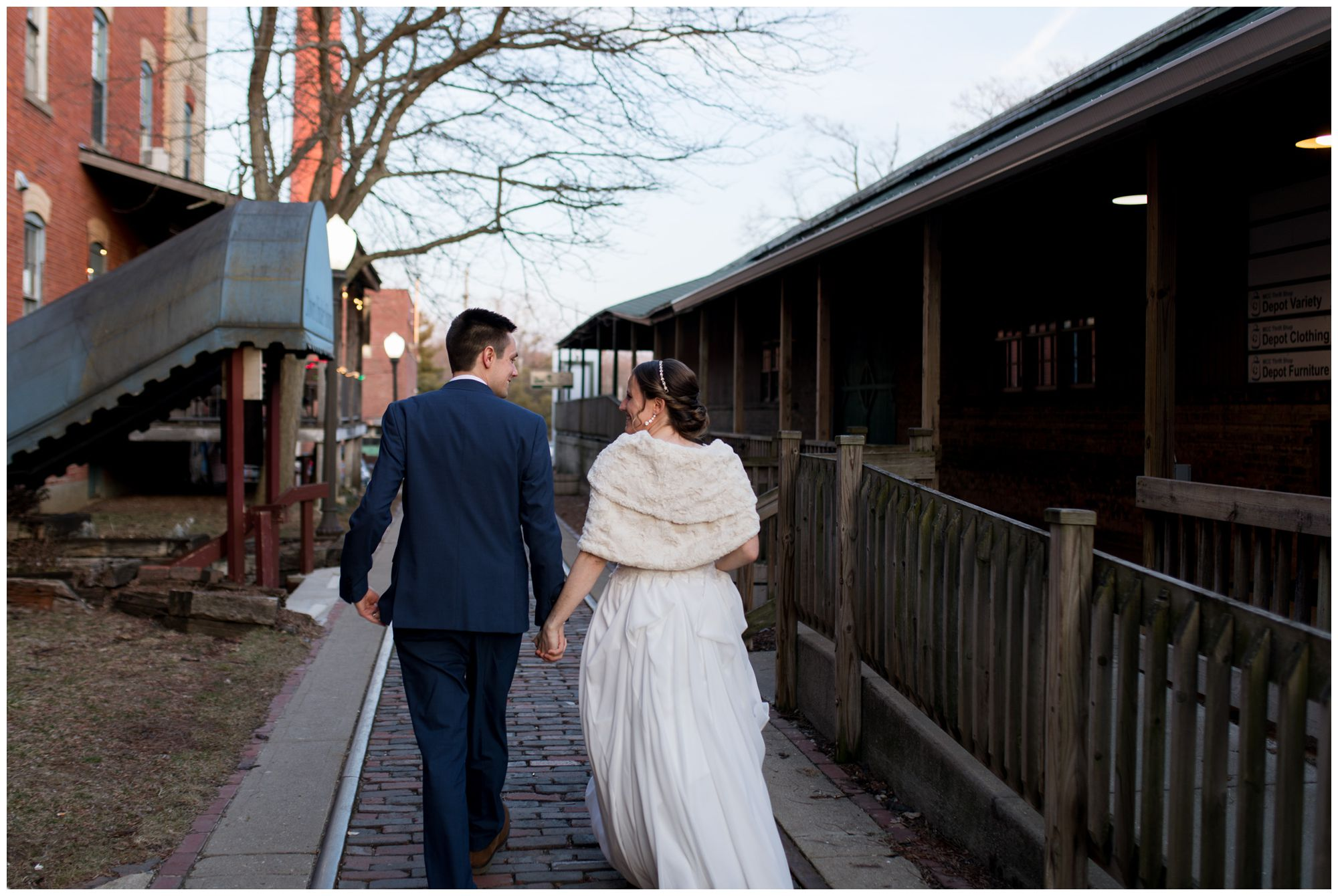 bride and groom walk hand in hand outside Old Bag Factory in Goshen Indiana