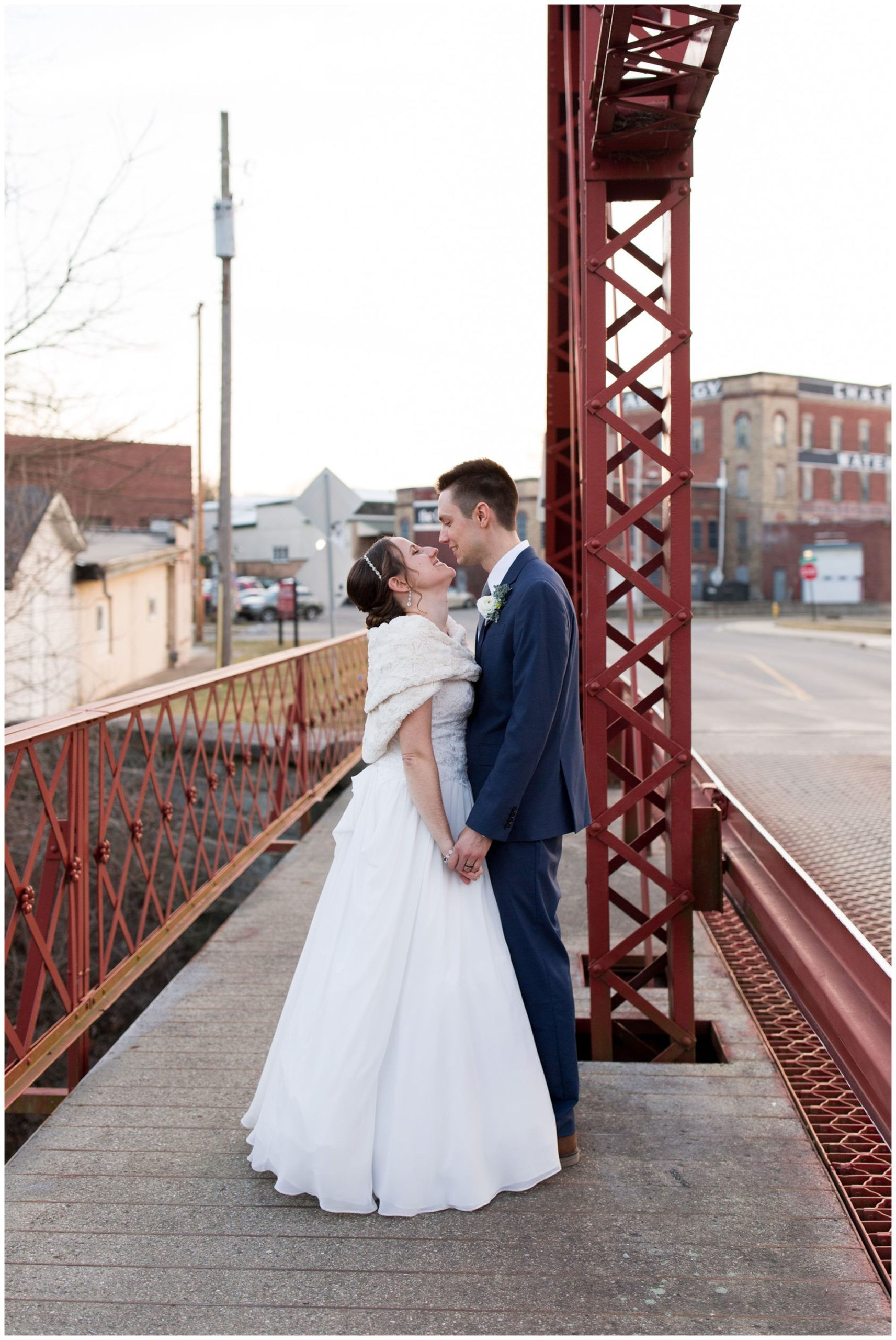 bride and groom kiss on bridge outside Old Bag Factory