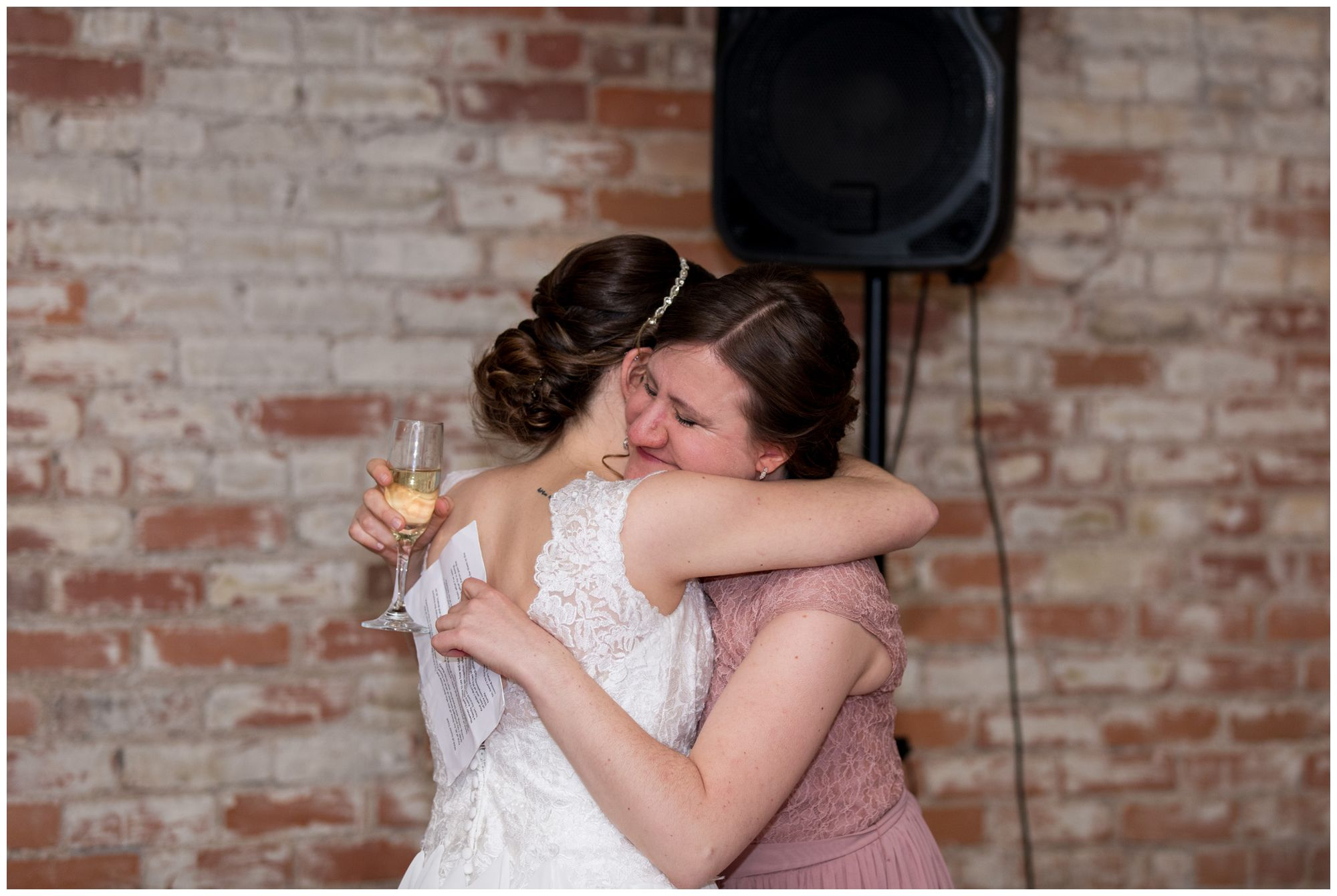 bride hugs maid of honor during industrial wedding reception