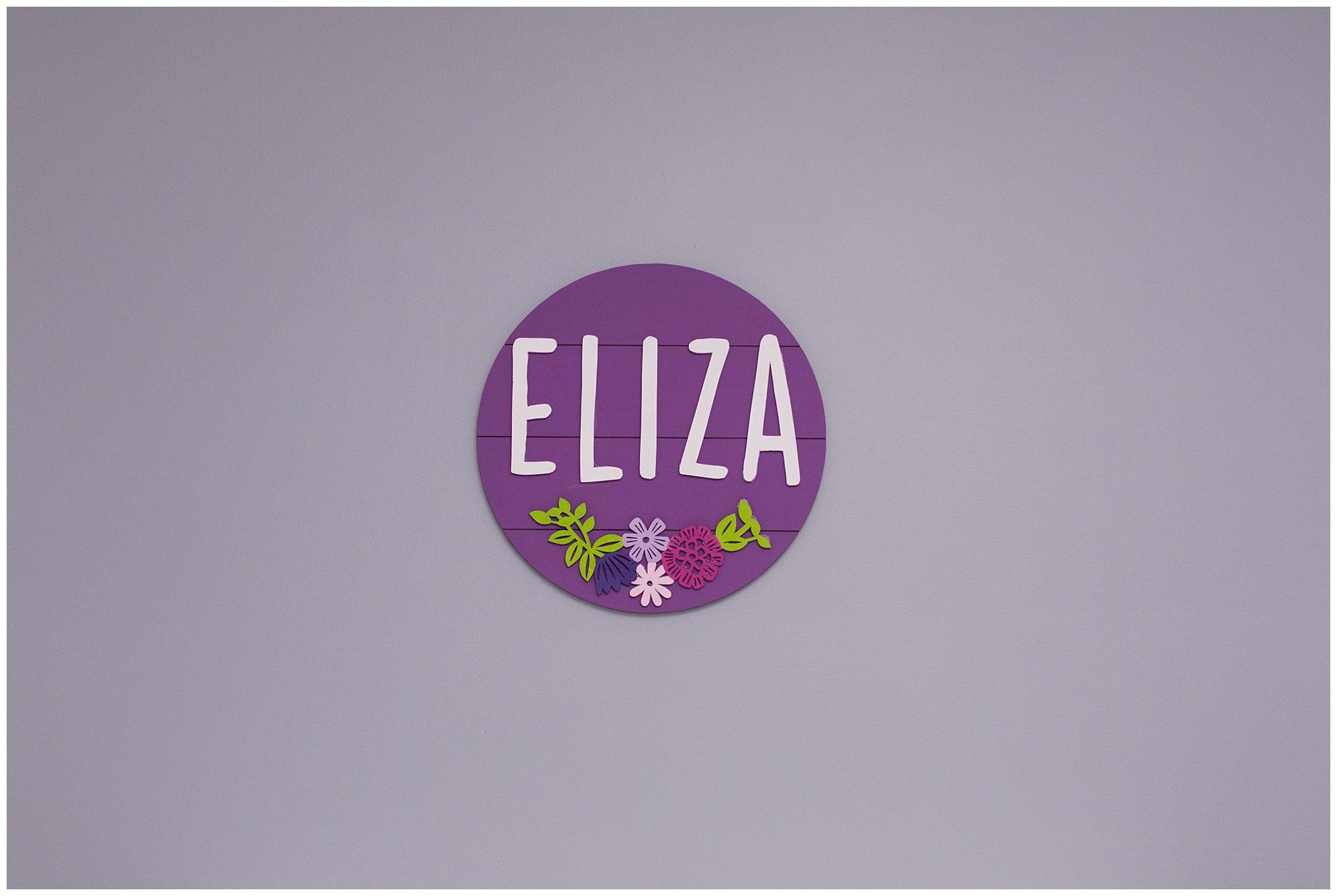 handmade sign that says Eliza in newborn's nursery