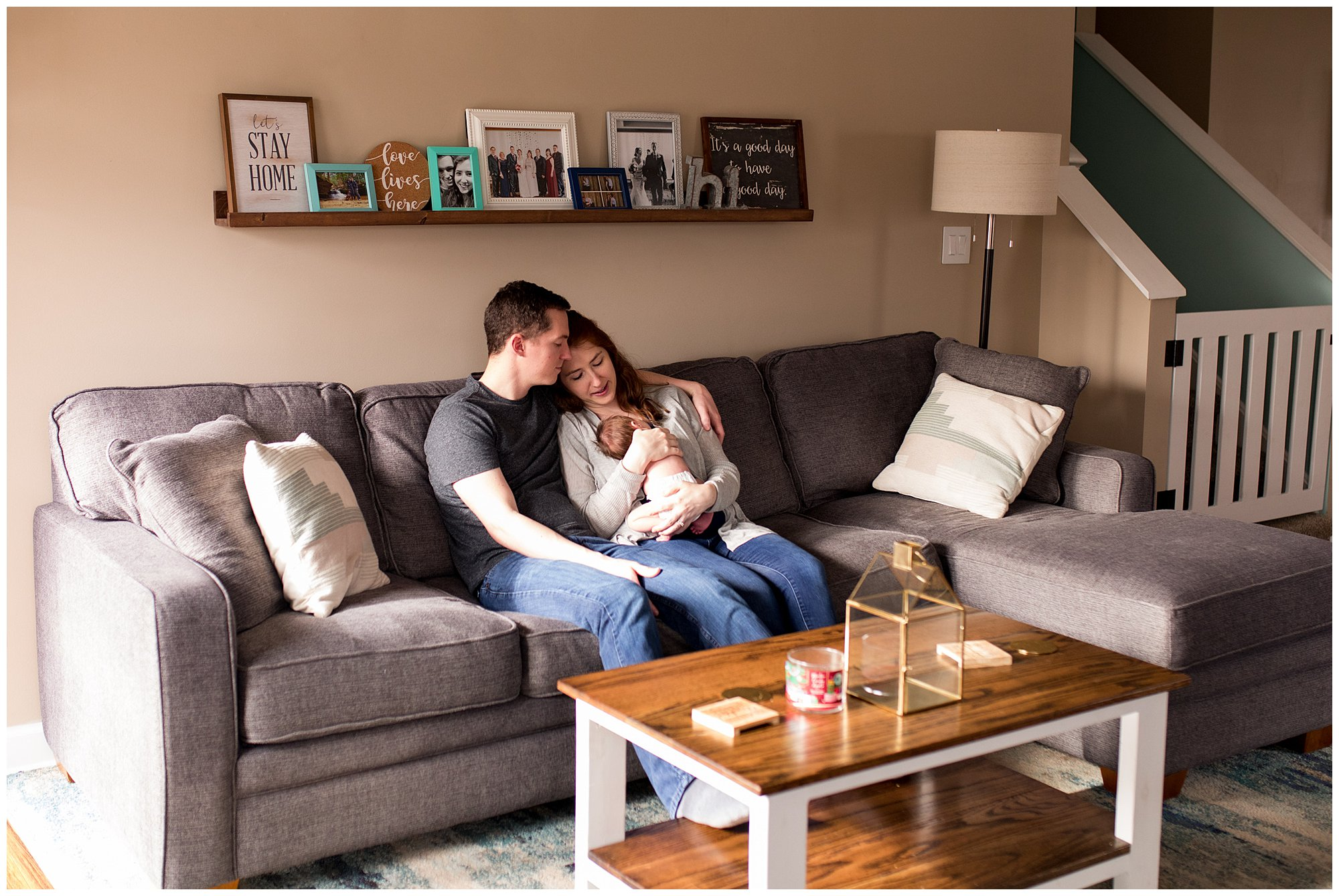 mom and dad sit on couch holding baby during newborn session in Columbus Indiana
