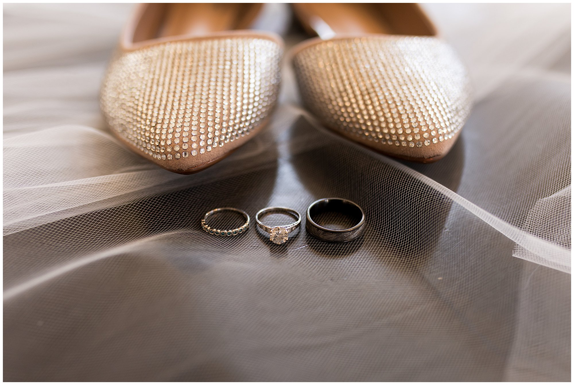 wedding rings in front of bride's shoes on top of her veil
