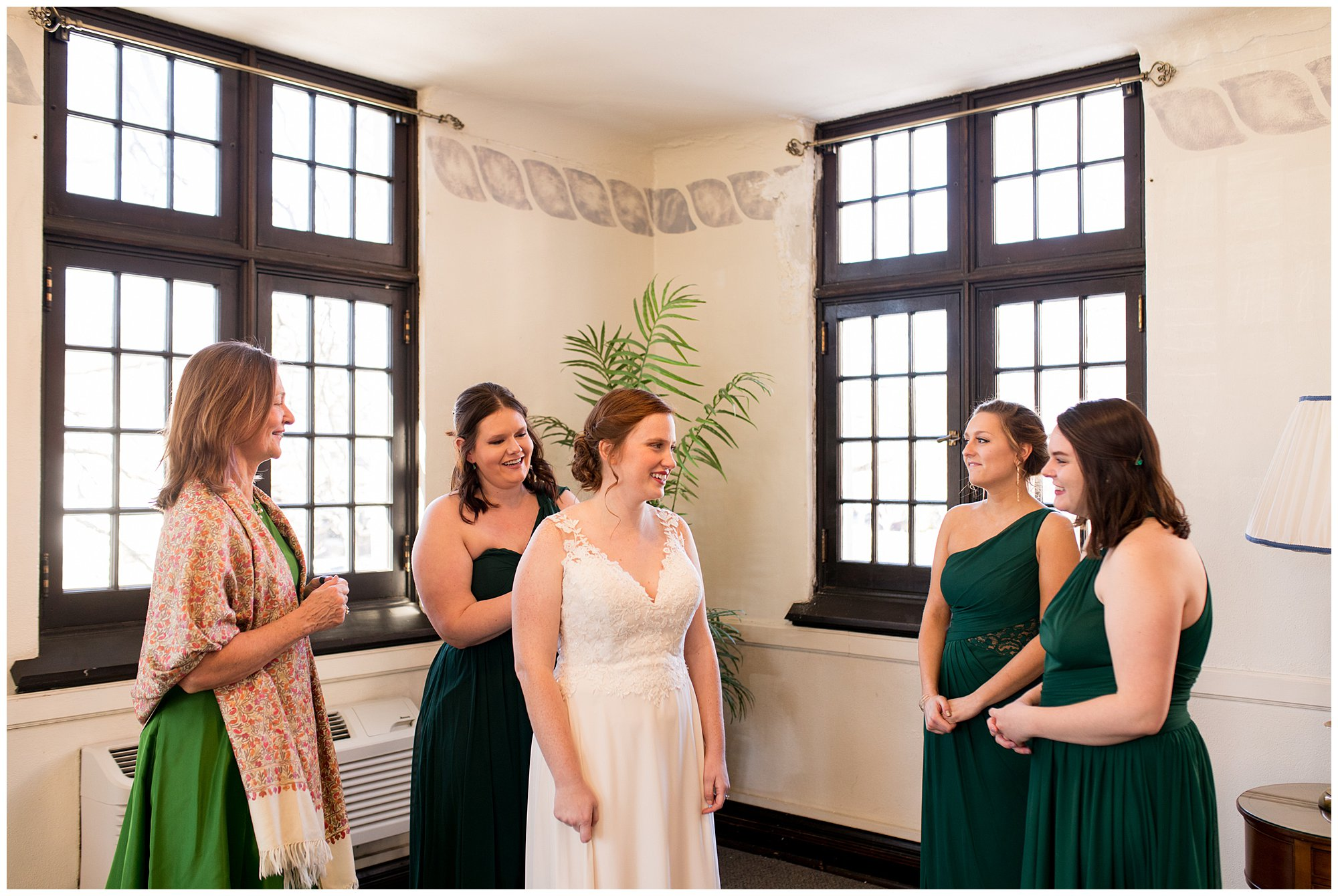 bride surrounded by bridesmaids helping her get ready before Indianapolis wedding ceremony