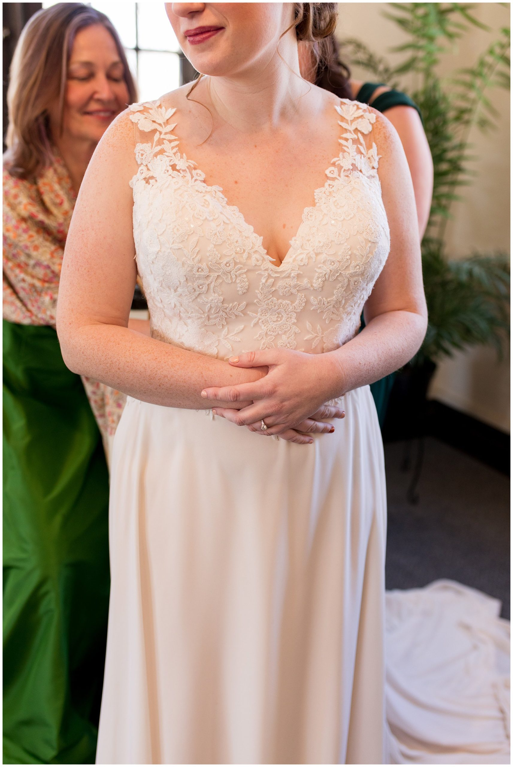 bride holding her hands while bridesmaids button her dress getting ready