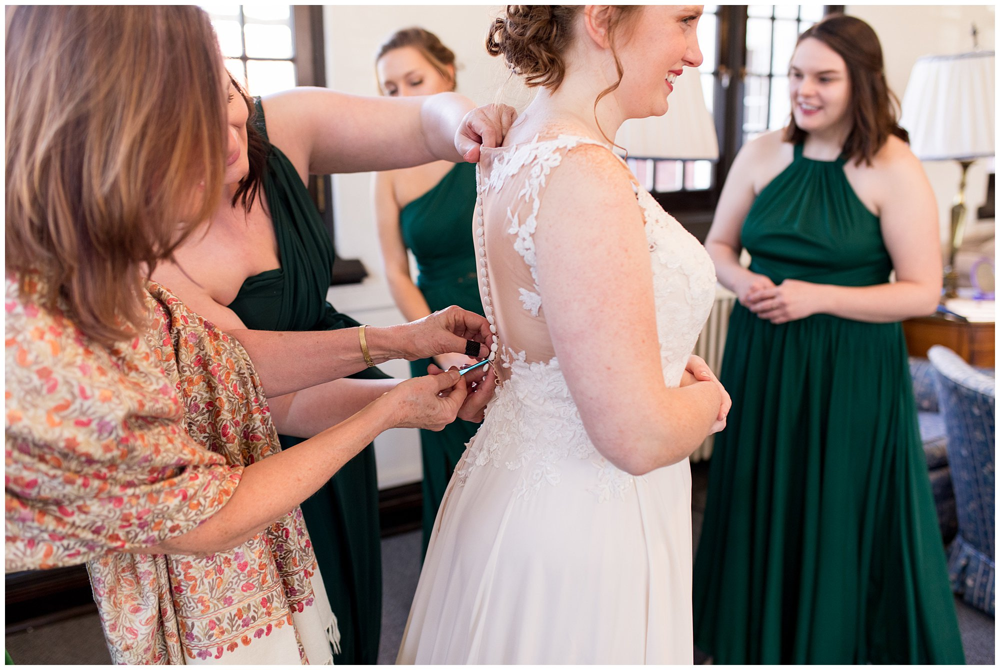 bridesmaids and mom button back of bride's dress before Indianapolis wedding ceremony