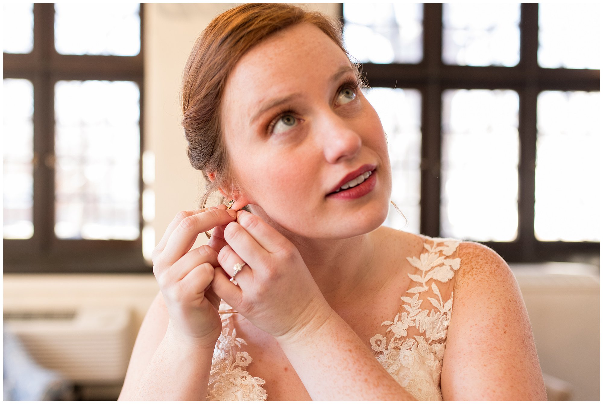 bride puts on earrings before Indianapolis wedding ceremony