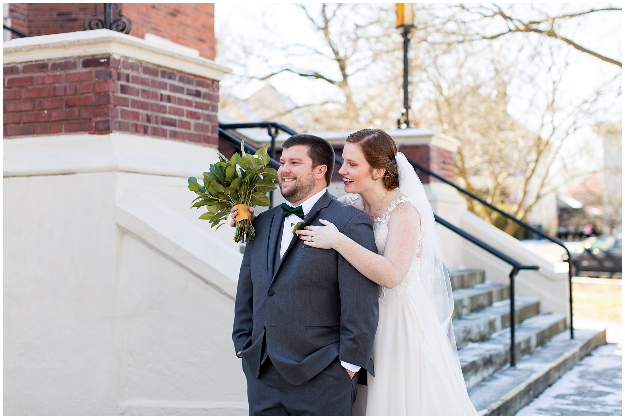 bride hugs groom from behind during first look at Irvington United Methodist Church in Indianapolis