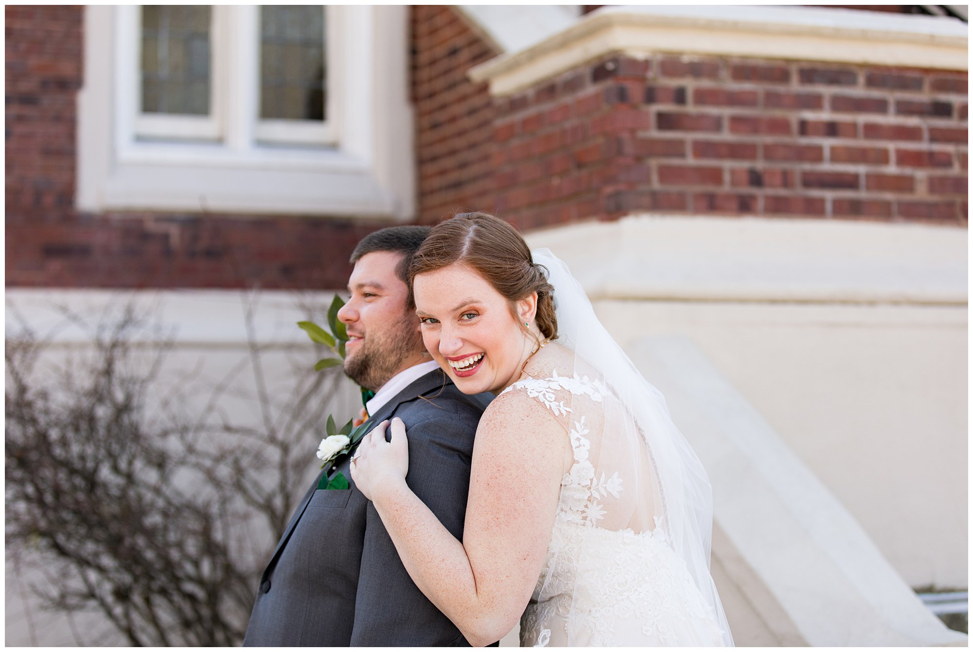 bride grabs groom from behind during first look before Indianapolis wedding