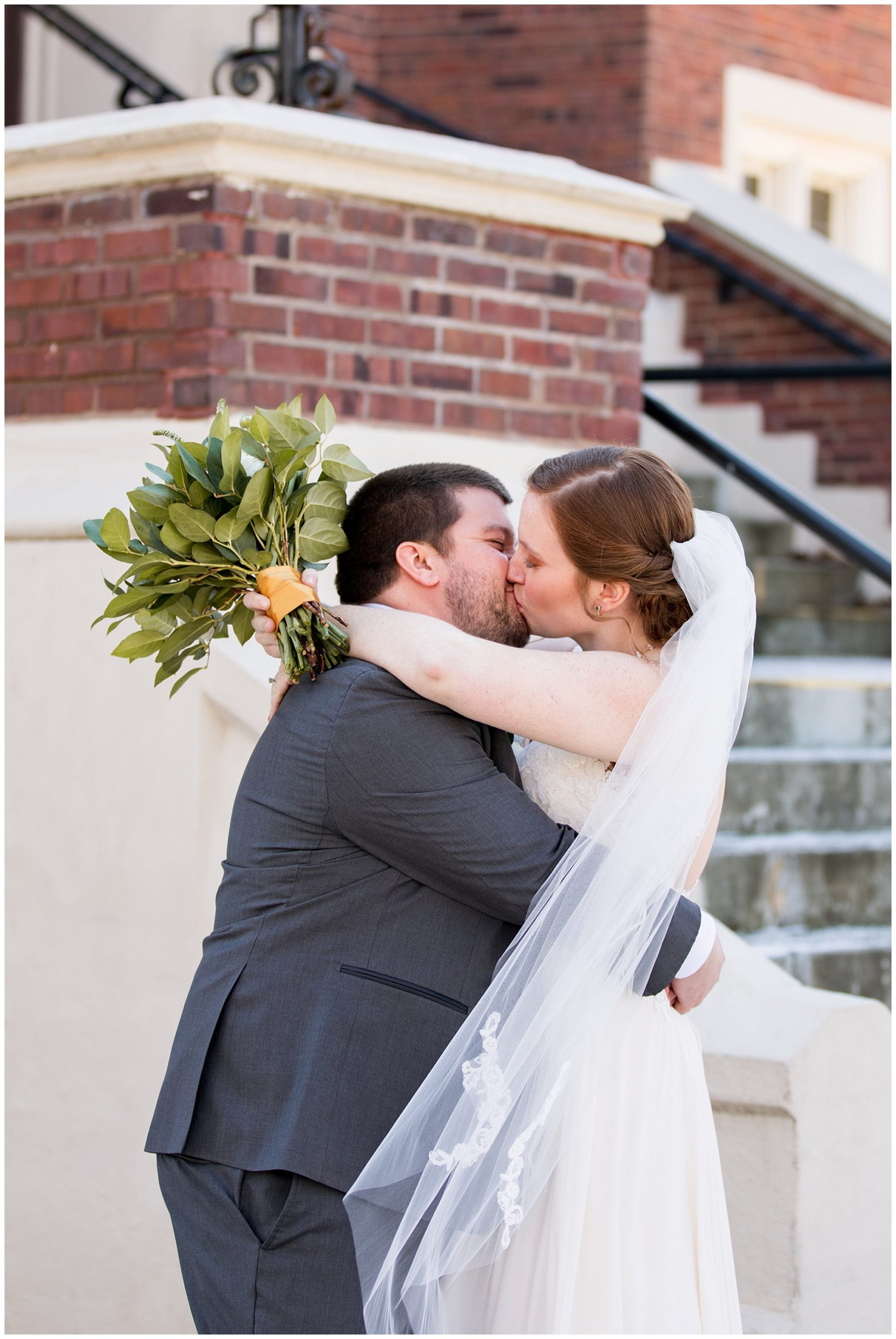 bride and groom kiss after first look outside of church