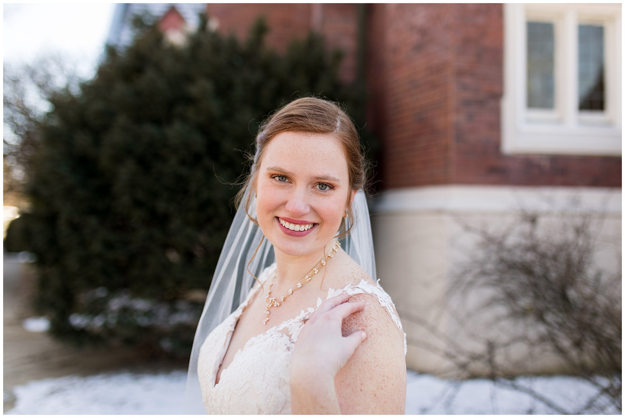 bride smiles with hand touching shoulder