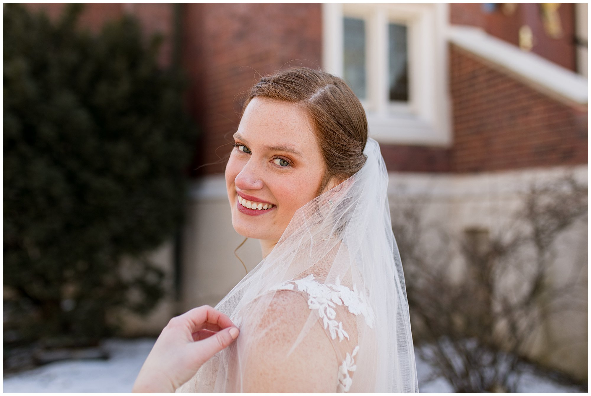 bride grabs at veil during wedding portraits