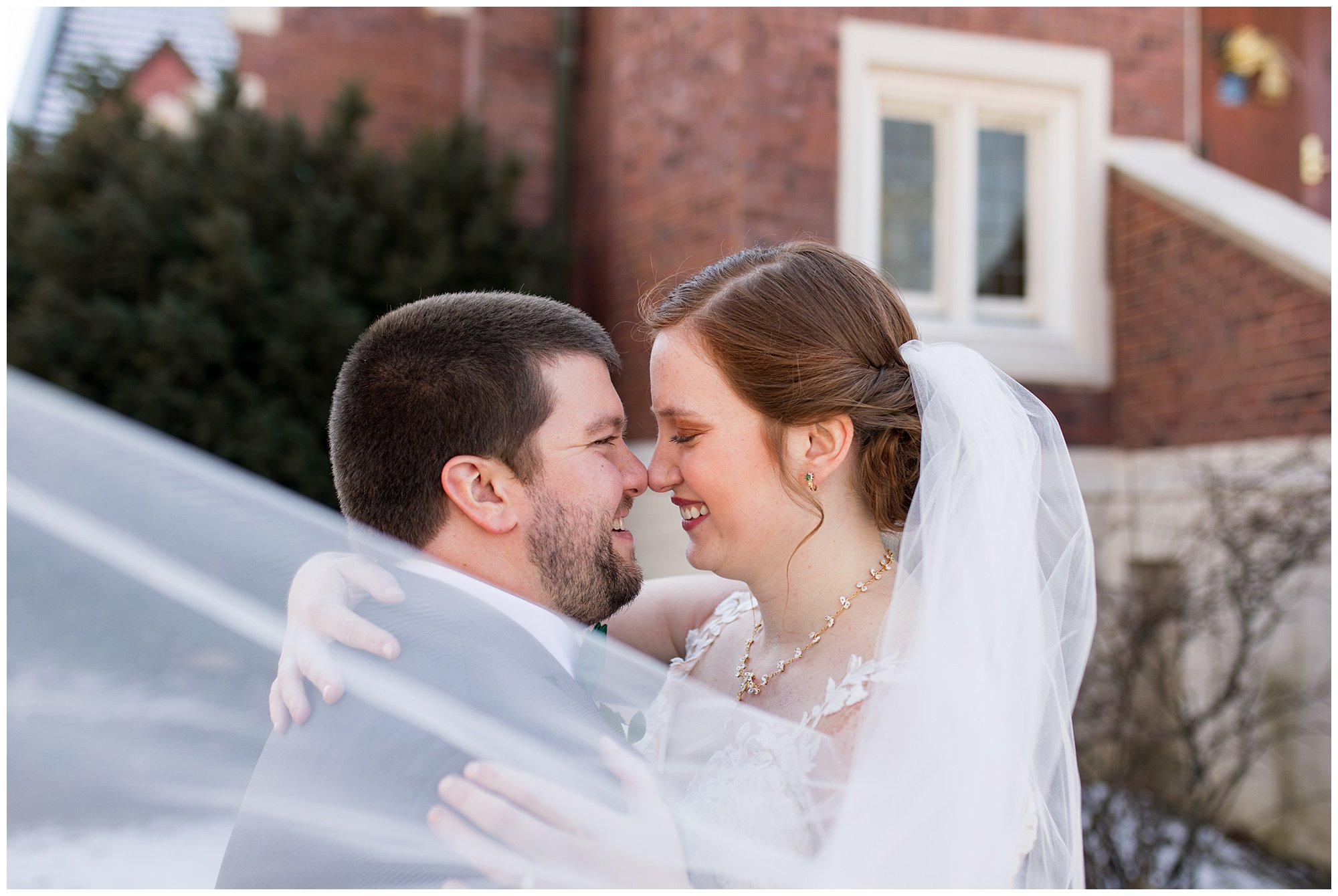 bride and groom wrap arms around each other with veil sweeping in front