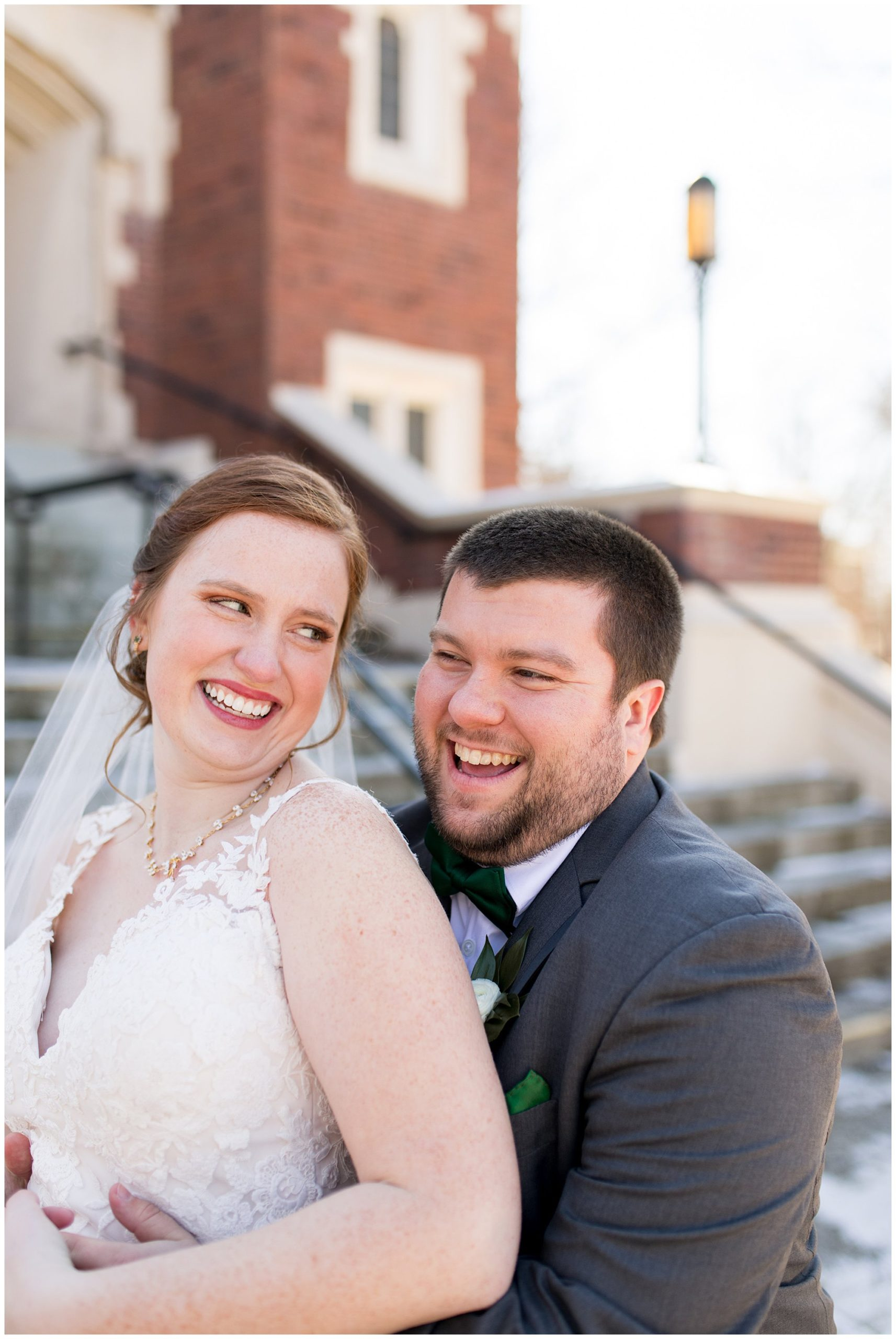bride and groom laugh together during wedding portraits