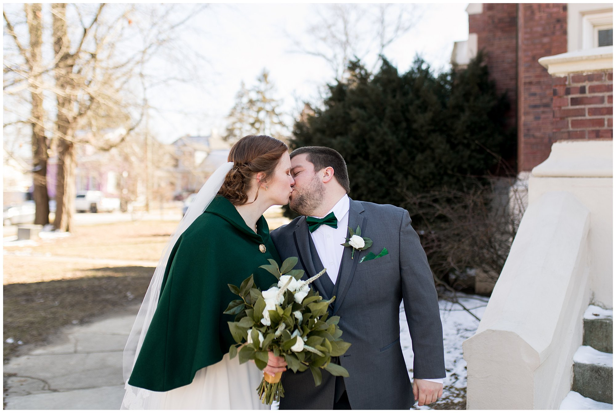 bride and groom kiss outside Irvington United Methodist Church in Indianapolis