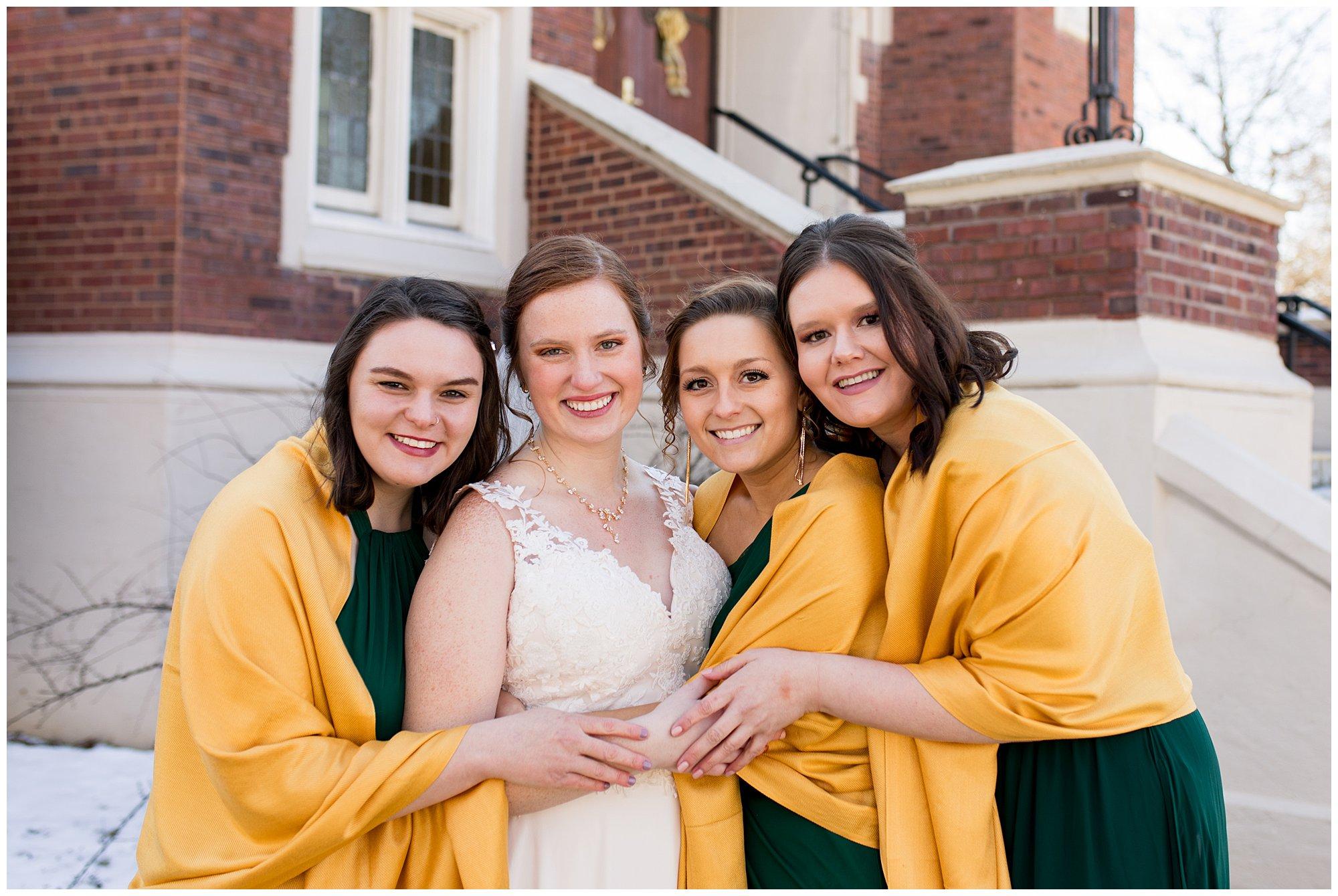 bride and bridesmaids snuggle close during wedding party photos